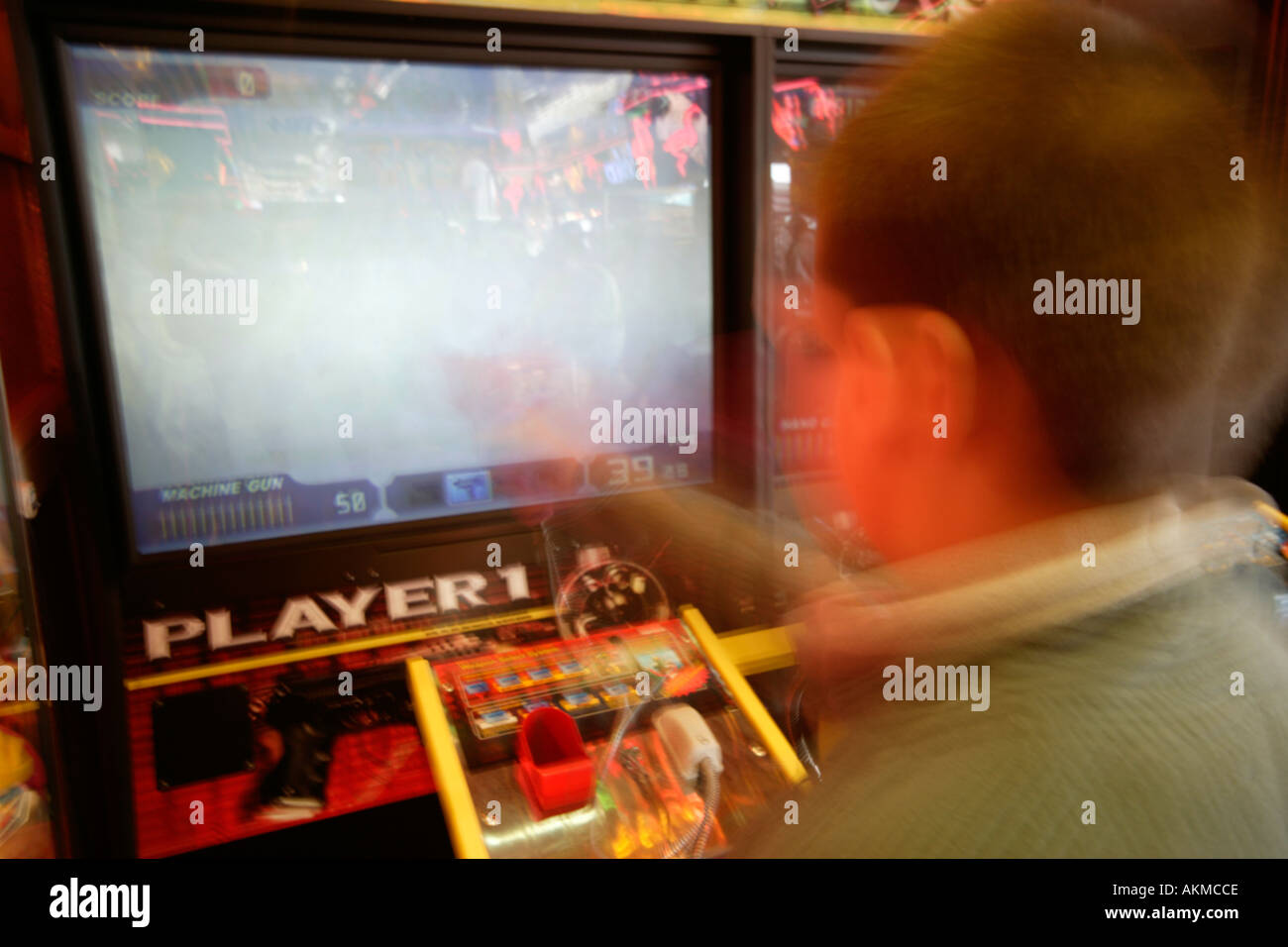 Boy Playing Shooting Game in Arcade - Stock Image