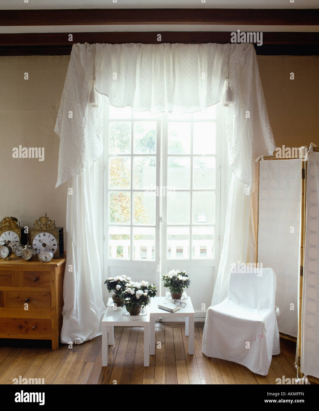 Small white table and white loosecover on chair in front of French doors with white voile curtains Stock Photo