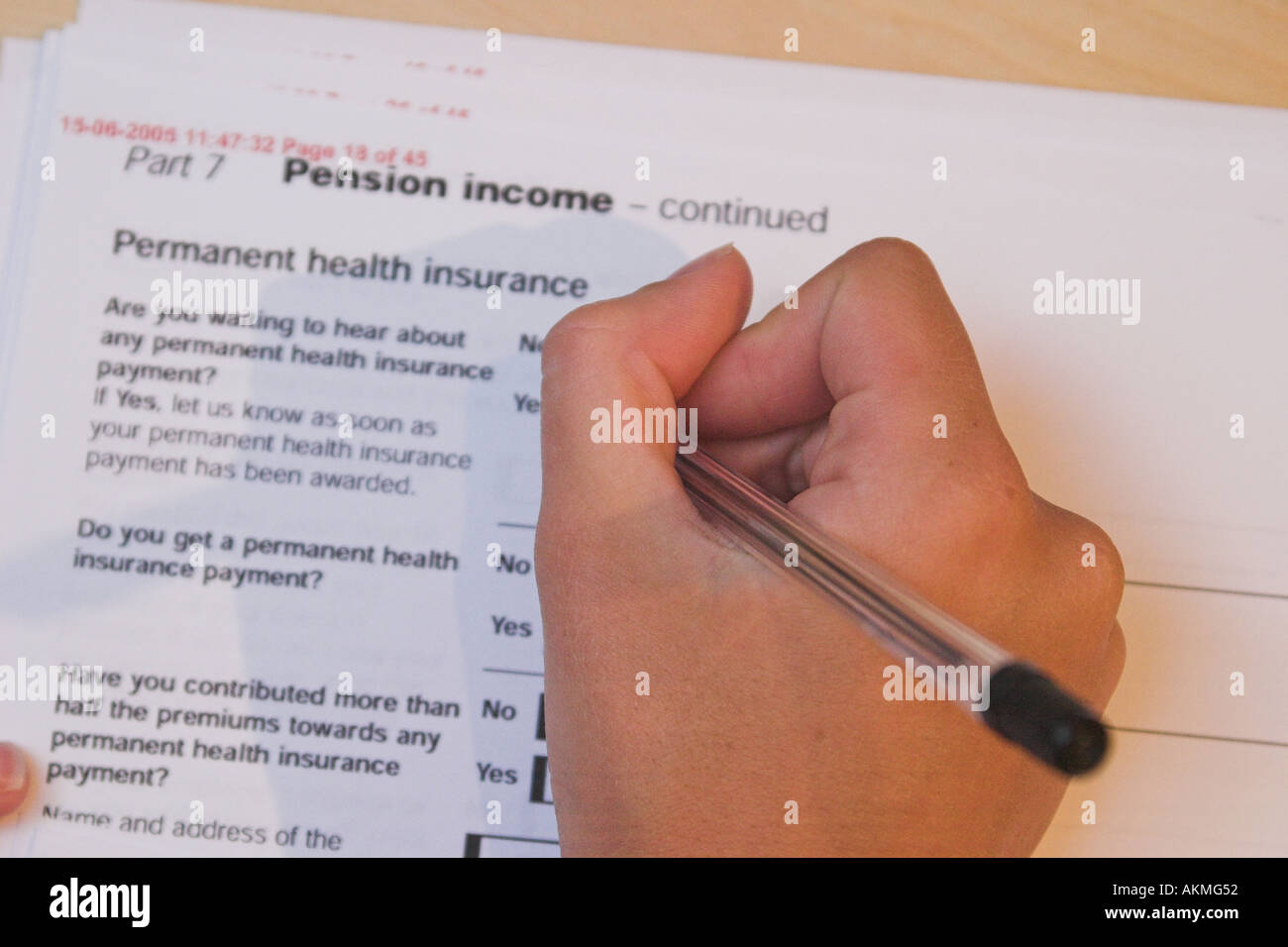 Lady filling out a Health Insurance form to claim income benefits from the government - Stock Image