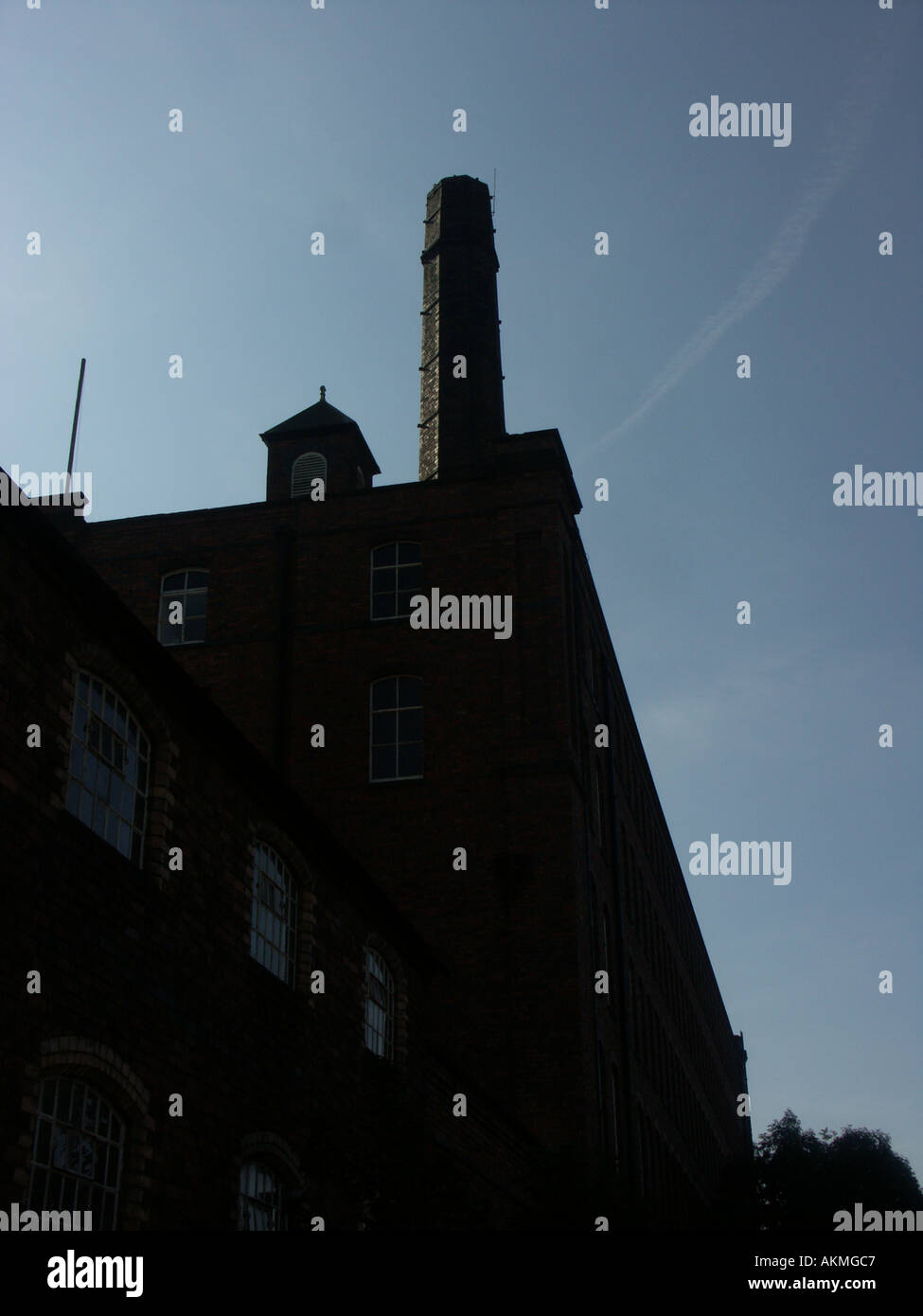 Tolsons Mill Fazeley near Tamworth showing typical tall chimney in silhouette against a blue sky. - Stock Image