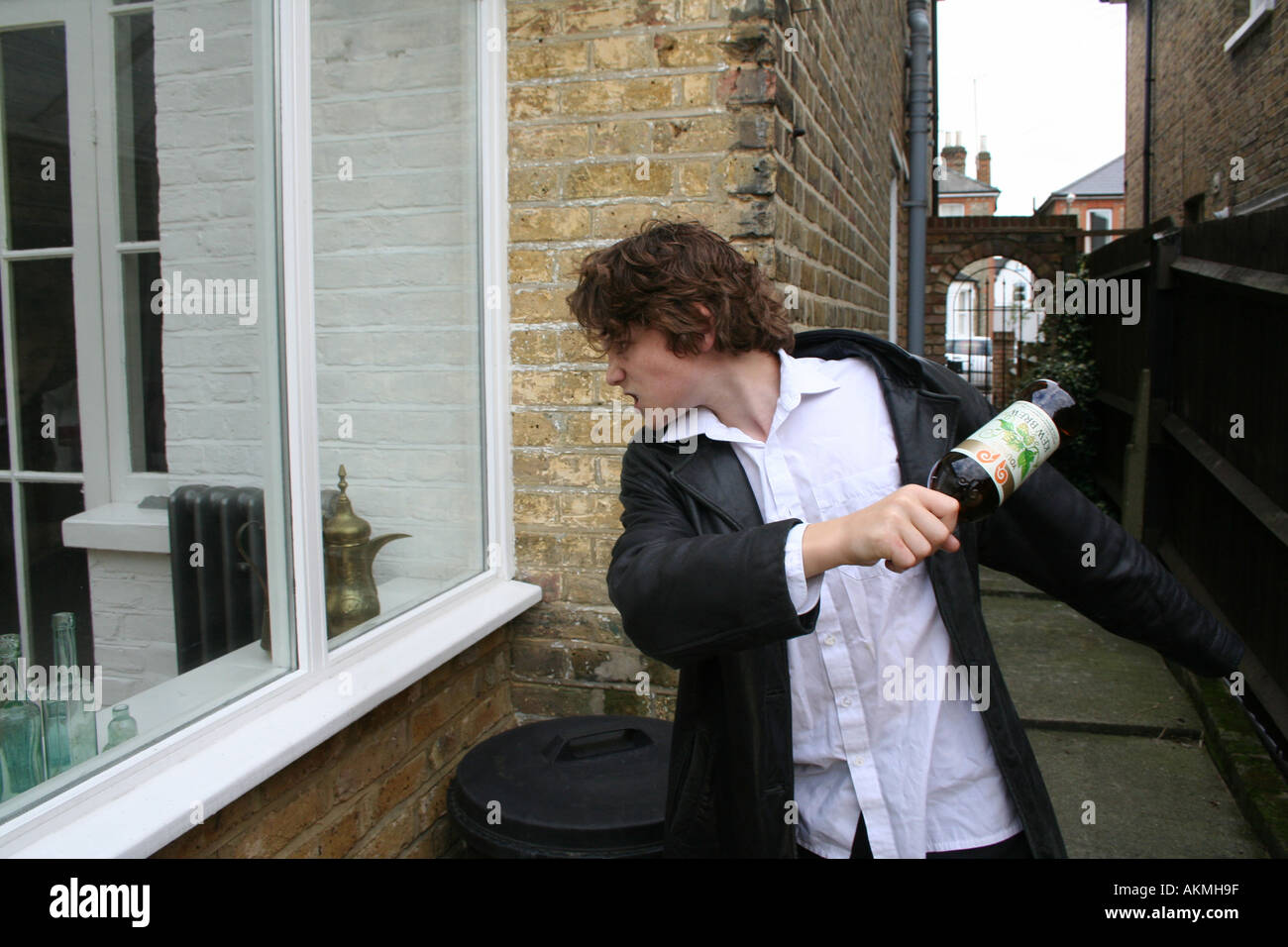 Young burglar breaking into a home with a bottle - Stock Image