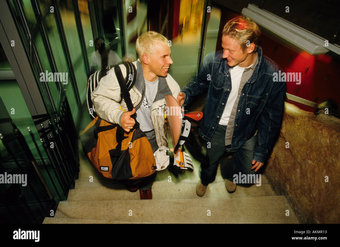 Germany Free time Two young men going up a staircase one of them is carriing a snowboard under his arm  - Stock Image