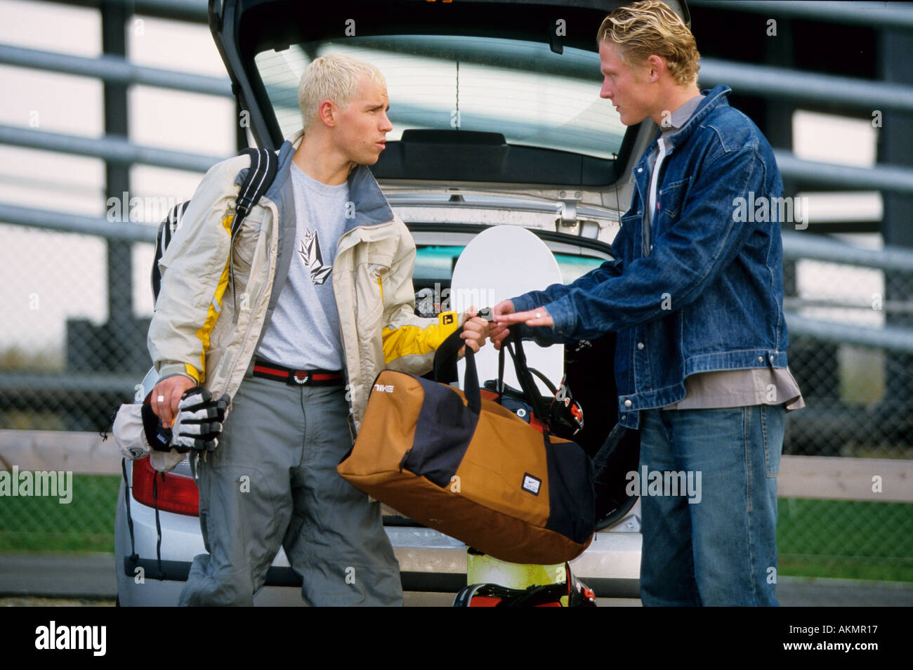Germany Free time Two young men next to a car they are putting their luggage into the boot  - Stock Image
