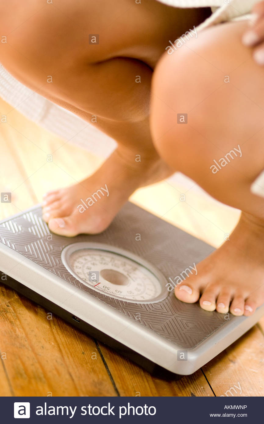 Girl weighing herself on scales - Stock Image