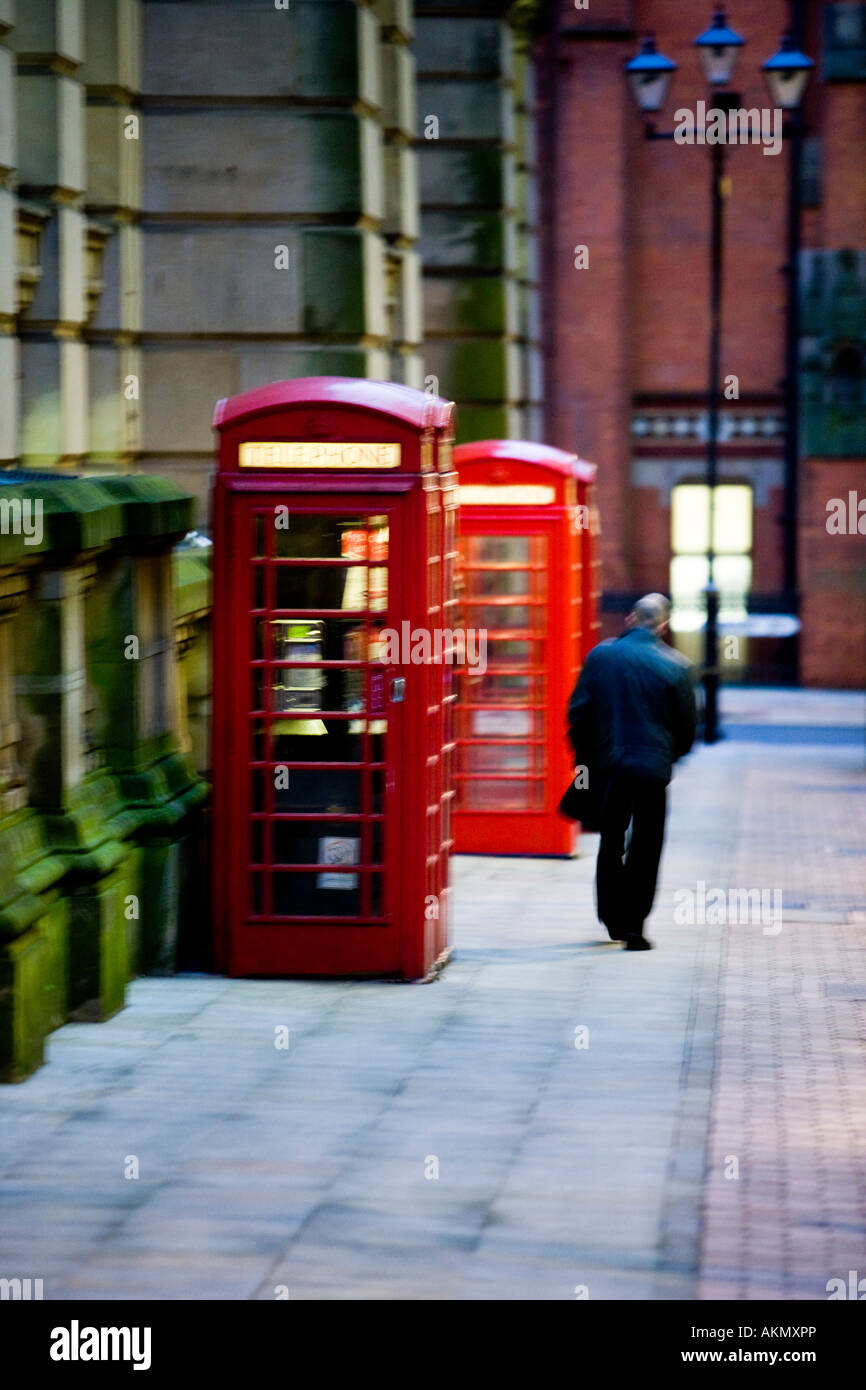 2 red phone boxes with man walking past. Birmingham. United Kingdom. - Stock Image