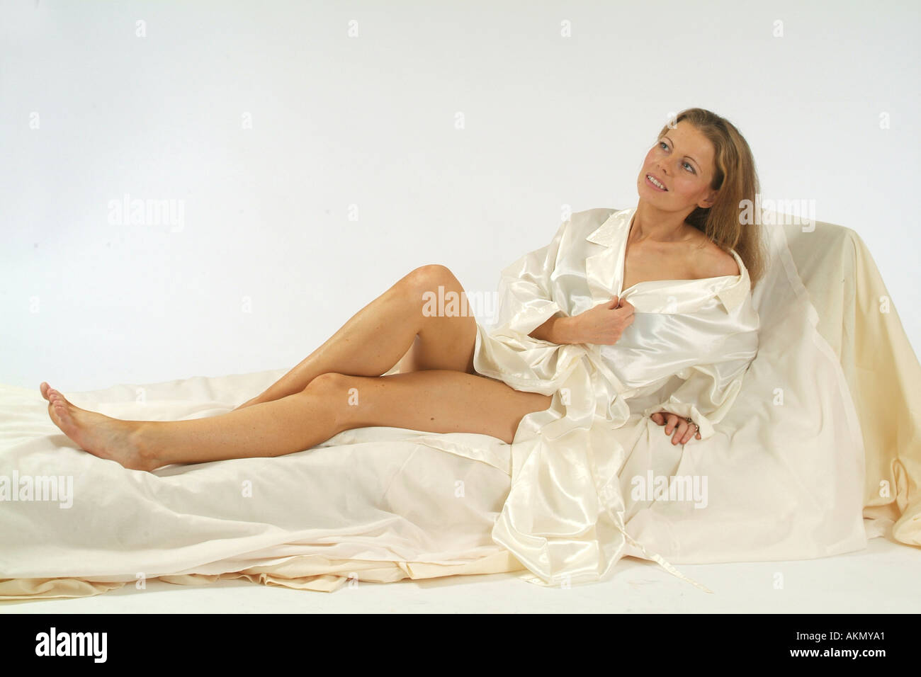 e315cfb662 A girl in her twenties wearing a white satin robe and sitting on a bed  looking
