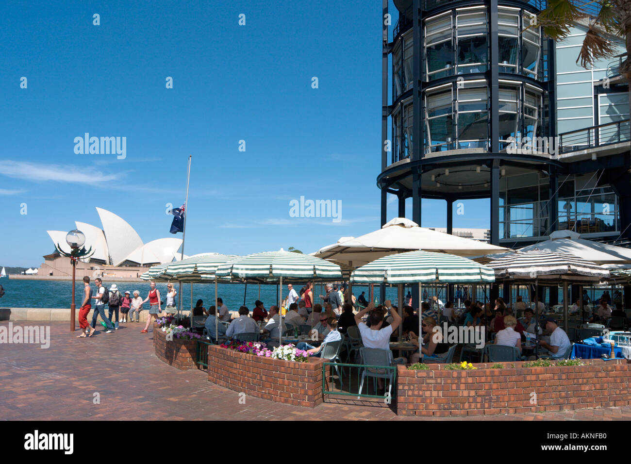 Pavement cafe in Circular Quay with the Opera House behind, Sydney, New South Wales, Australia - Stock Image