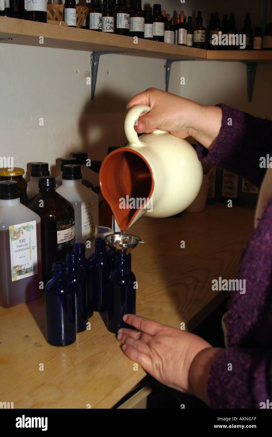 a woman pouring herbal oils into a bottle during the manufacturing process of natural oils - Stock Image
