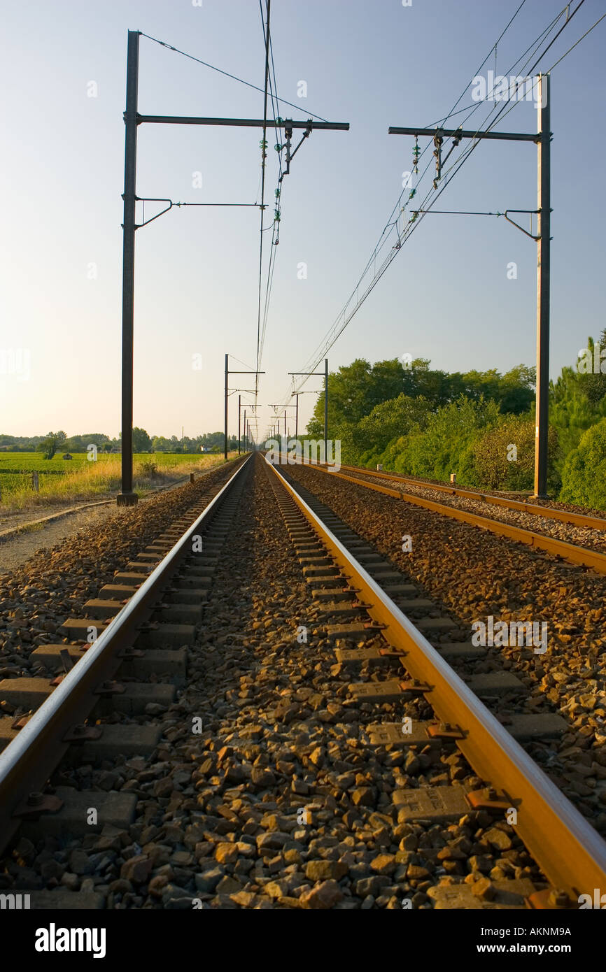 Train track and overhead cables at level crossing near Barsac station Bordeaux region France - Stock Image