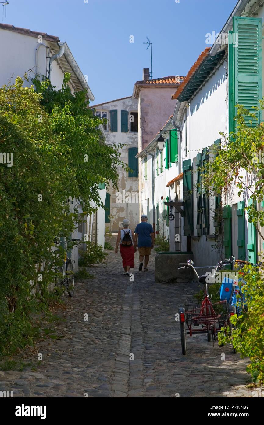 A couple walking down a cobbled street St Martin, Il de Re,France - Stock Image
