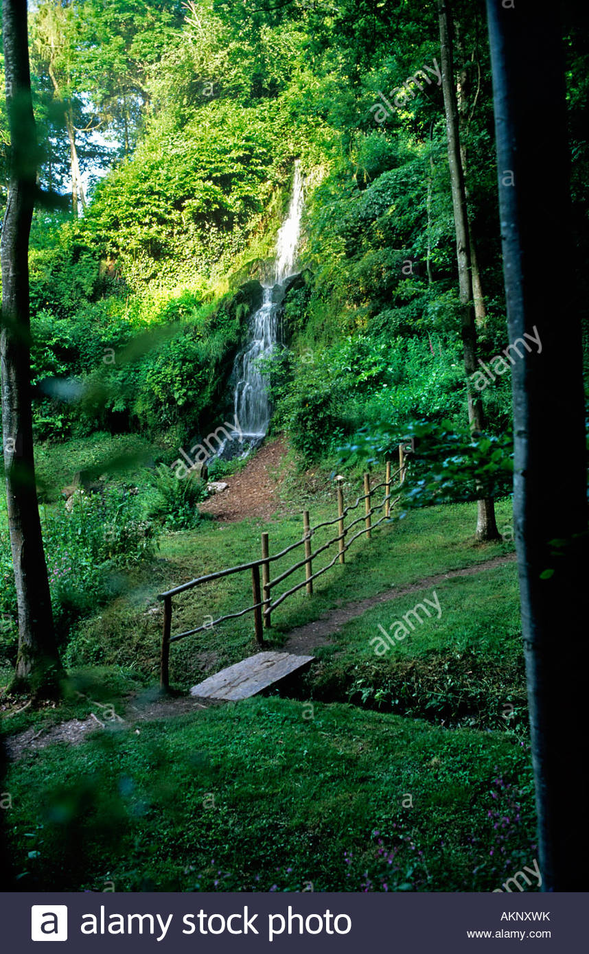 Waterfall glade in the woodlands Rustic fence leading along pathway to small bridge Hestercombe Gardens Somerset - Stock Image
