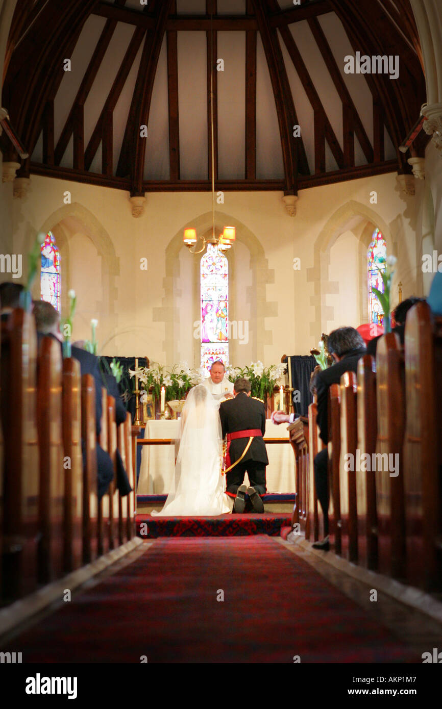 Bride and groom kneel at altar during typical catholic wedding stock bride and groom kneel at altar during typical catholic wedding ceremony in ancient village church junglespirit Image collections