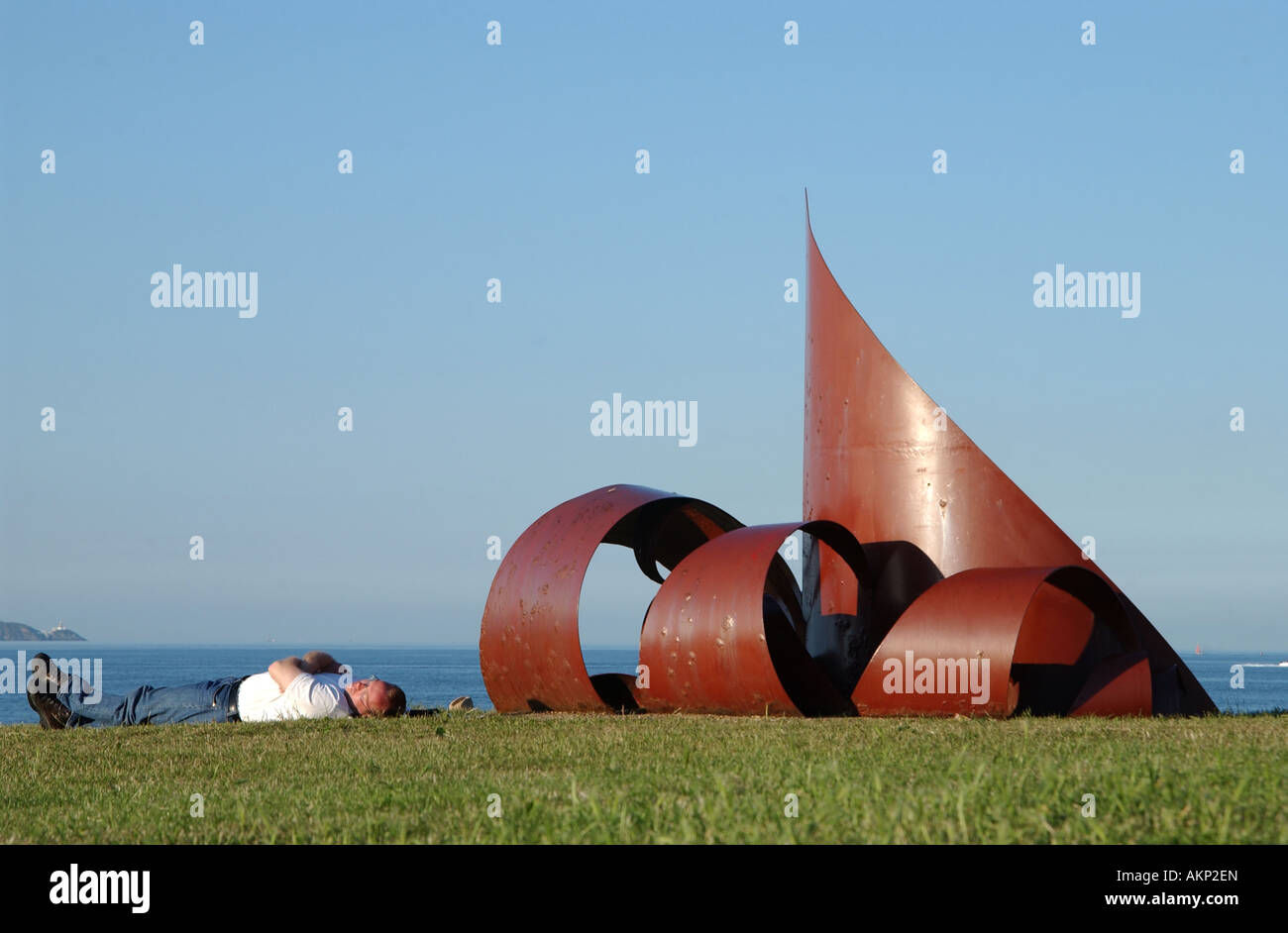 A man takes a nap beside some public art on a hot summers day in Dun Laoghaire, Co. Dublin, Ireland. - Stock Image