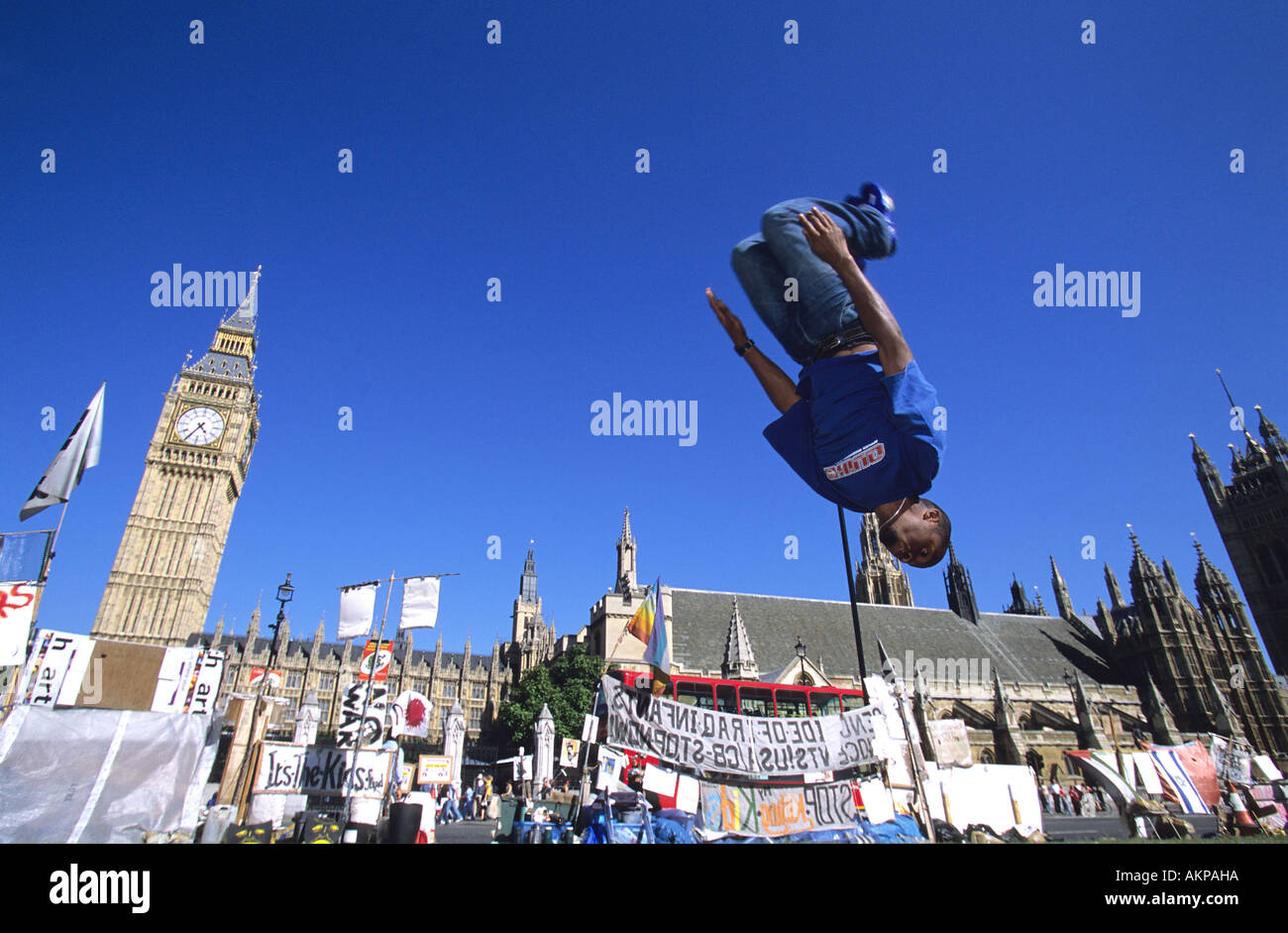 Le Parkour enthusiast back flipping outside the Houses of Parliament and Big Ben in London - Stock Image