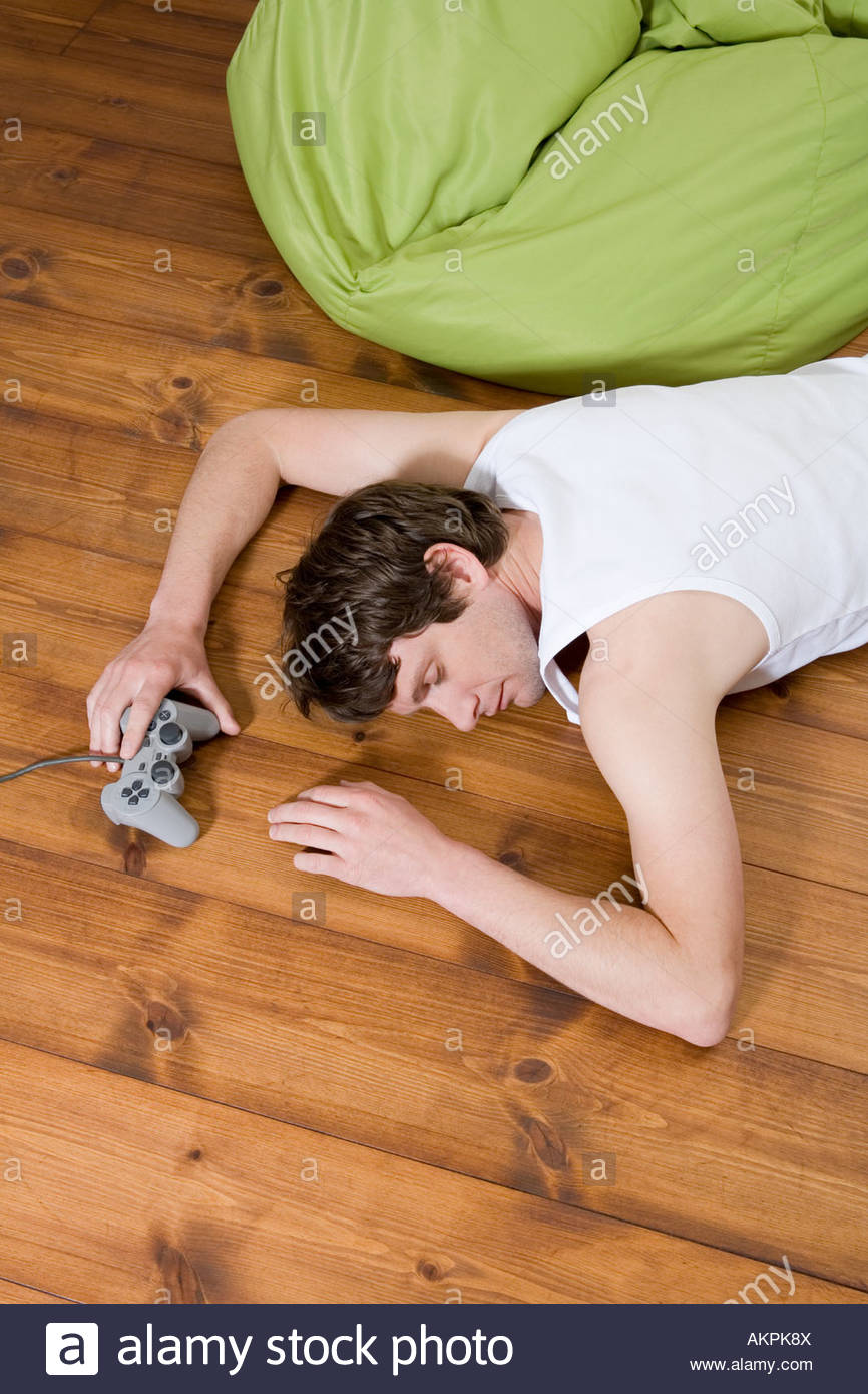 Sleeping man with video game controller - Stock Image