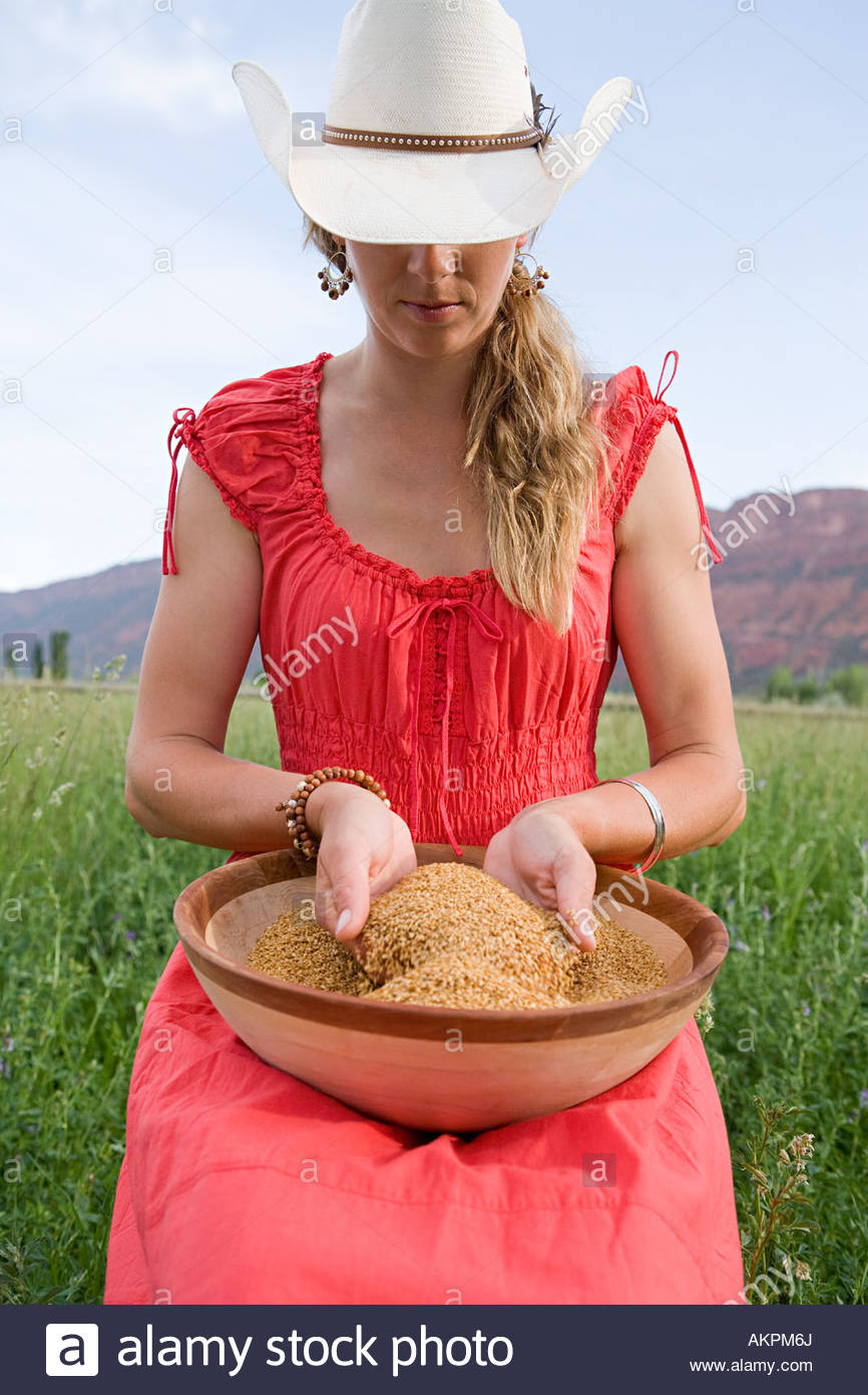 Woman with bowl of grain - Stock Image