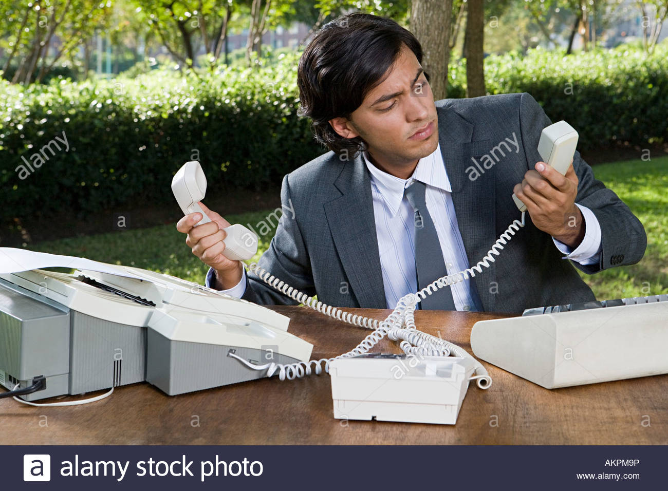 Man taking telephone calls in a park - Stock Image