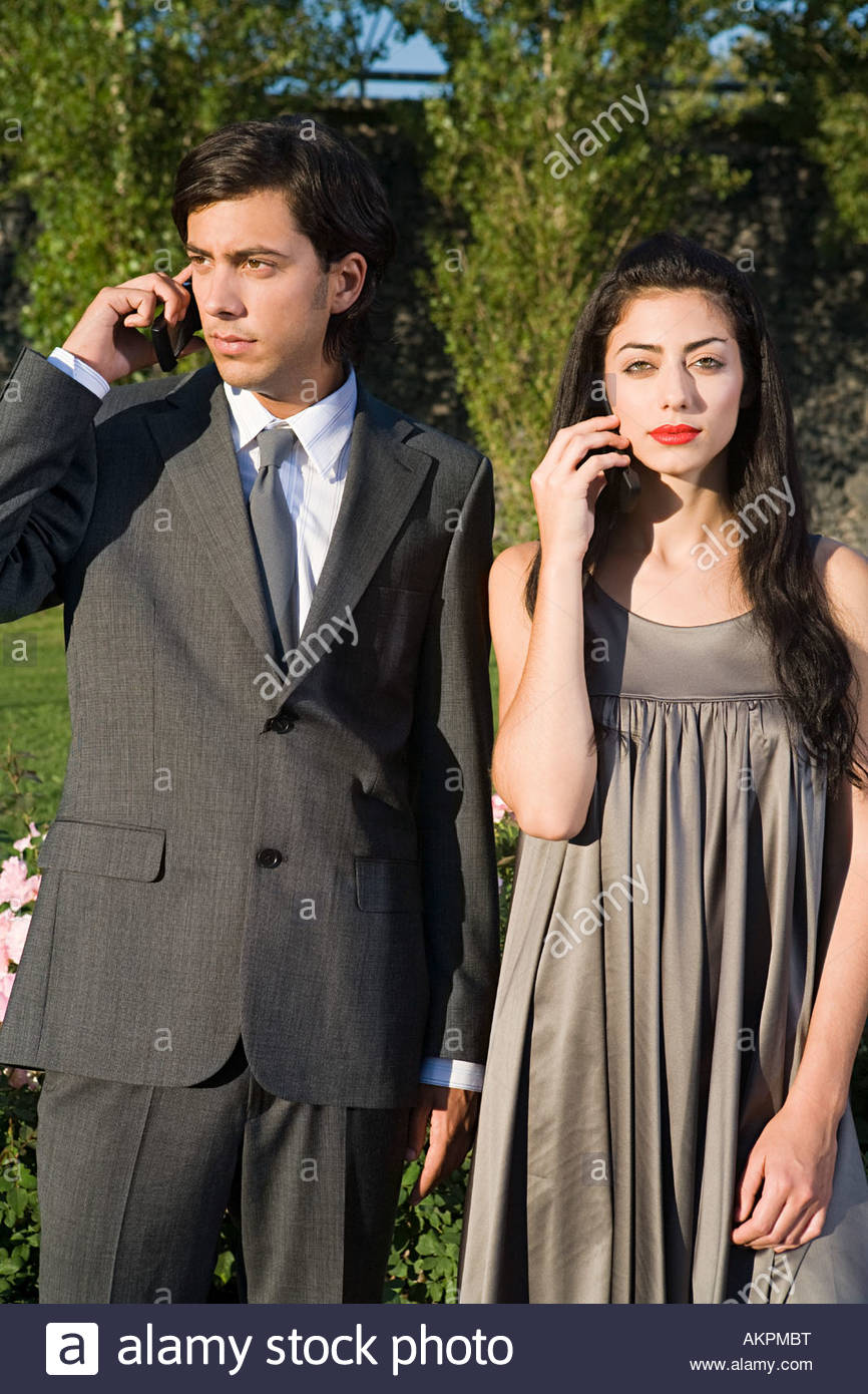 Two people using cellular telephones - Stock Image