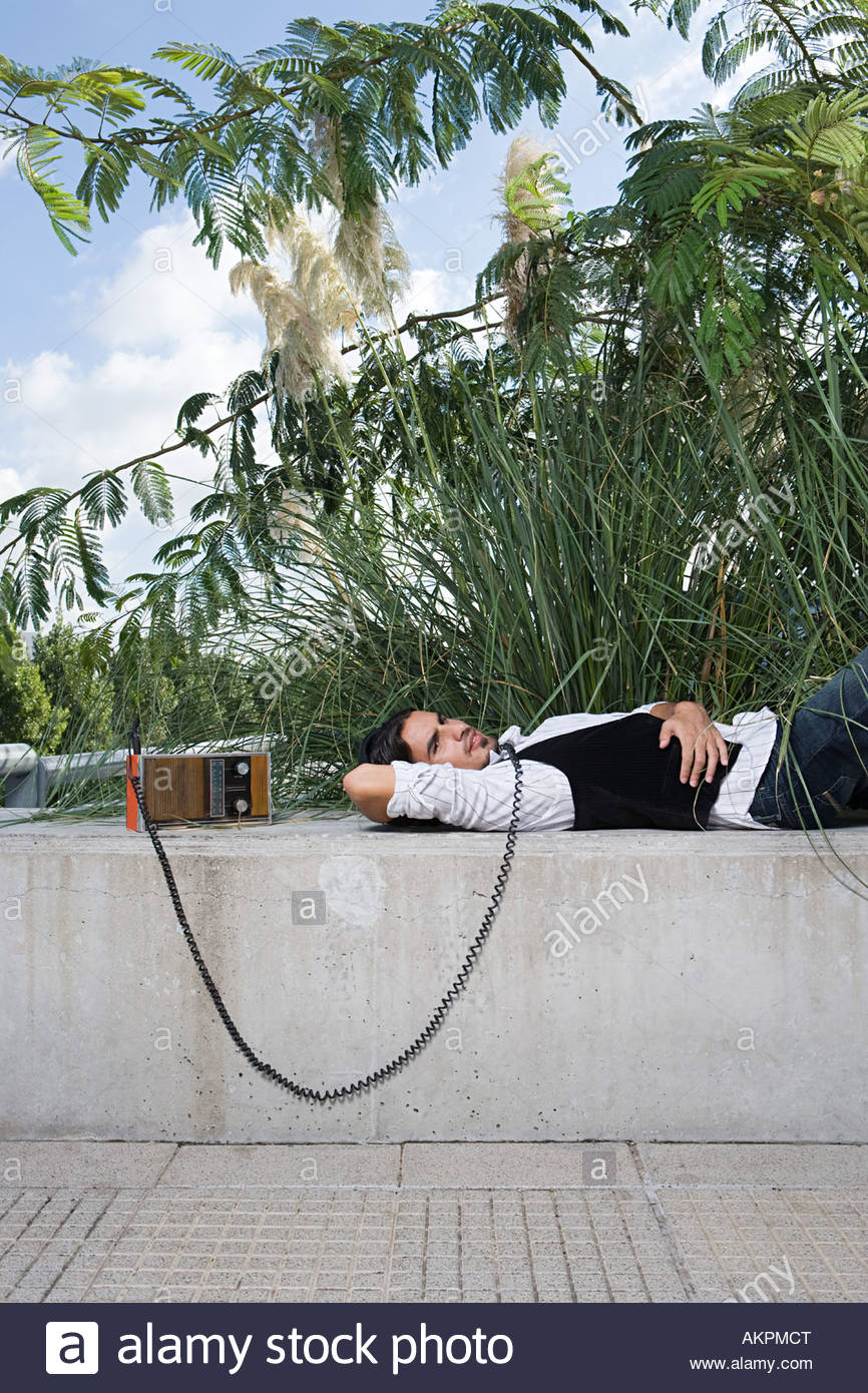 Man listening to radio on a wall - Stock Image