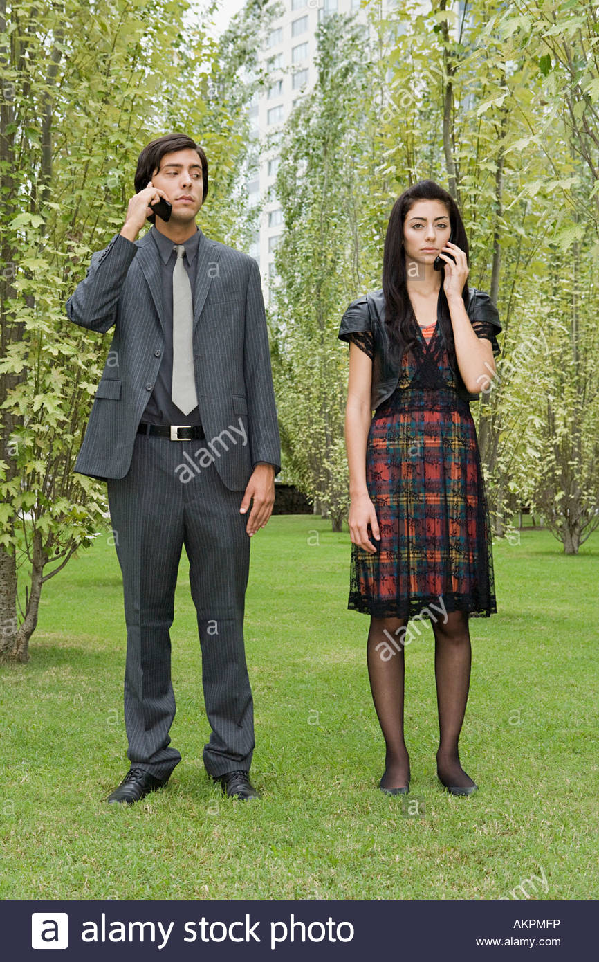 Man and woman using cellular telephones - Stock Image