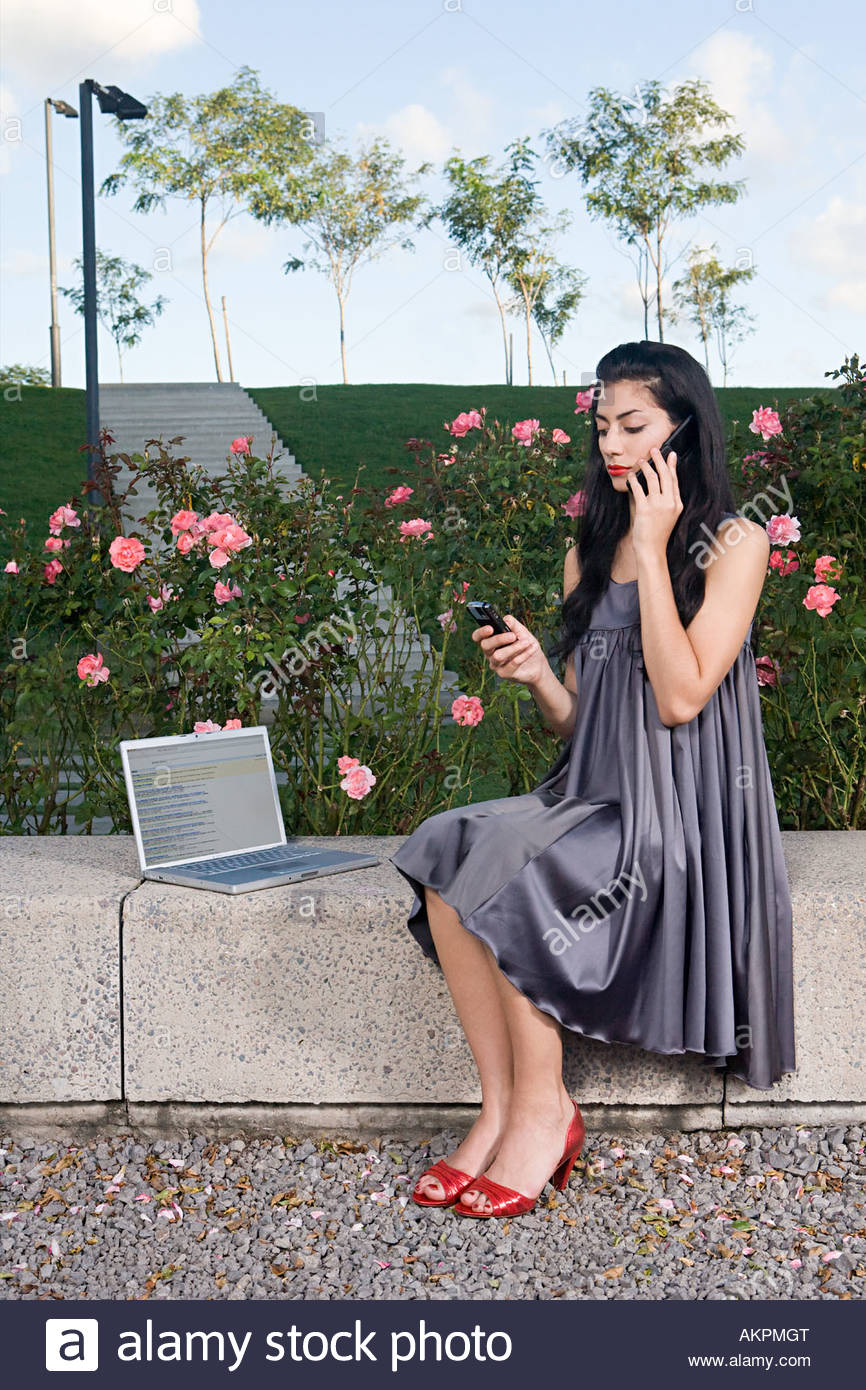 Woman using laptop and cellular telephones - Stock Image