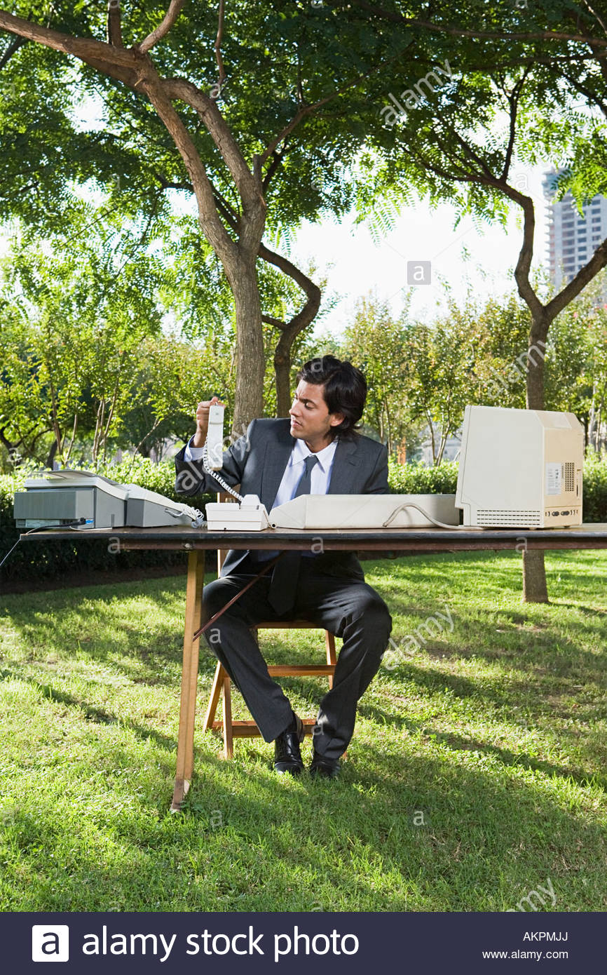 Businessman using old computer in park - Stock Image