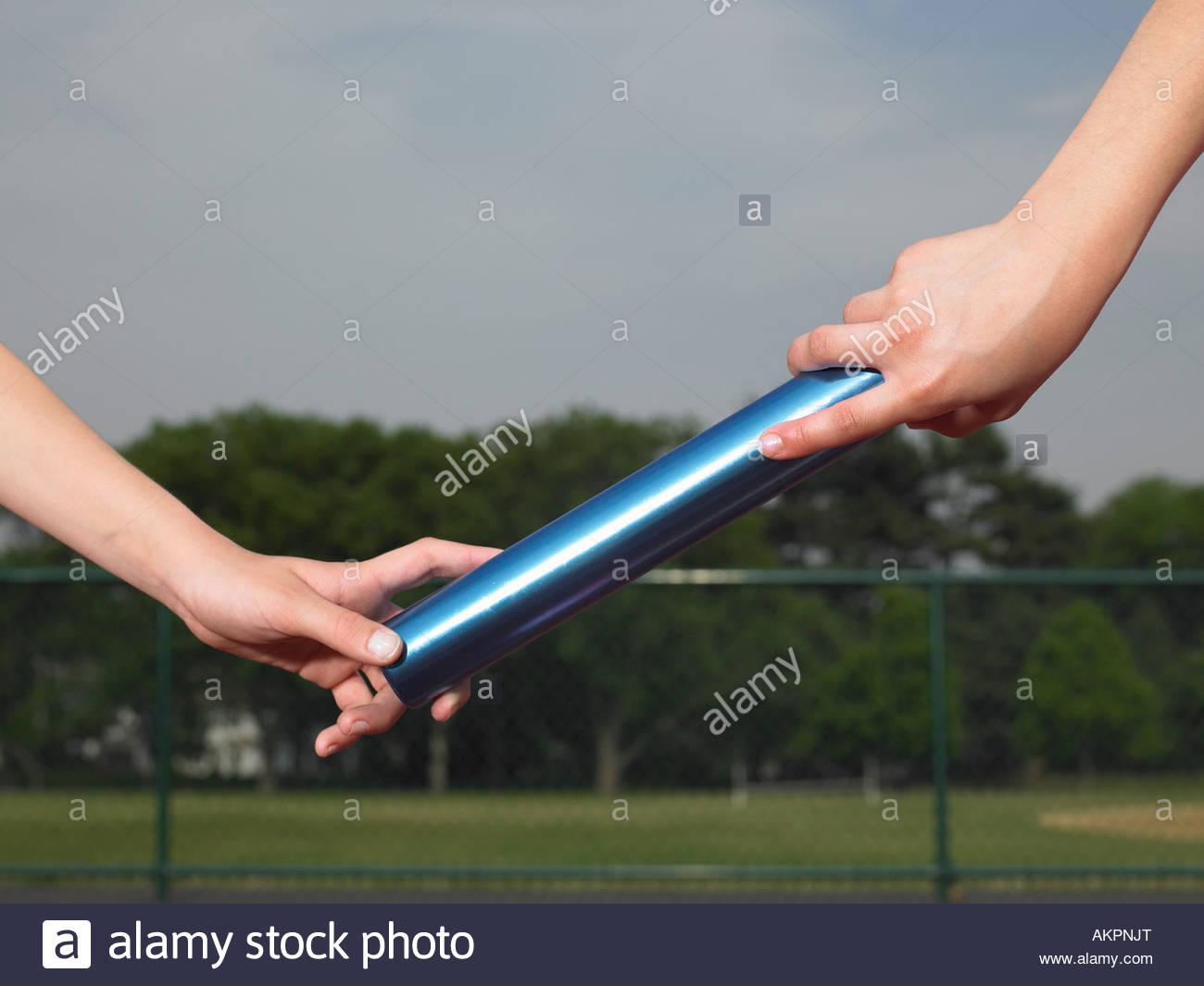 A person passing a baton - Stock Image