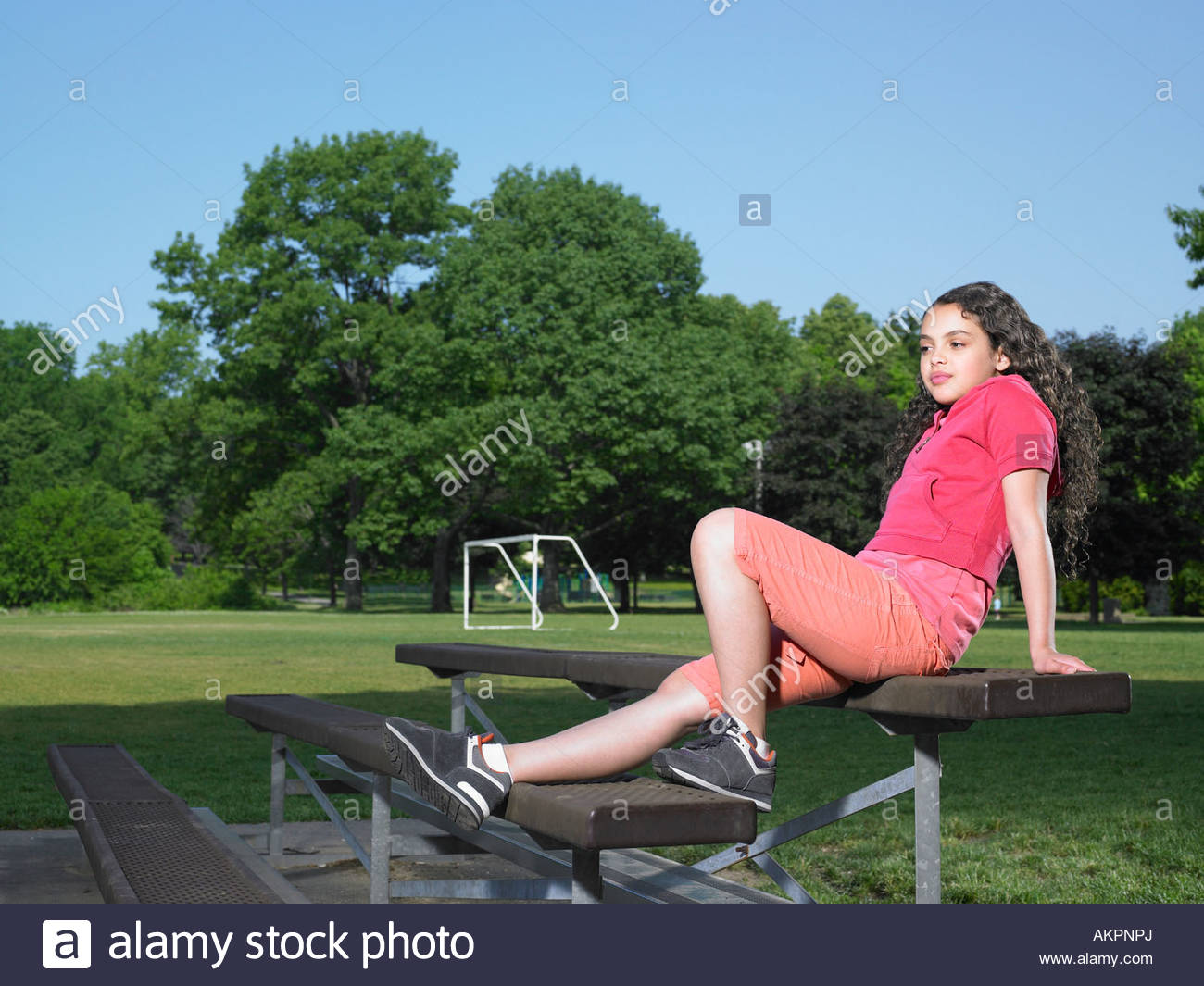 A girl sat on a bench - Stock Image
