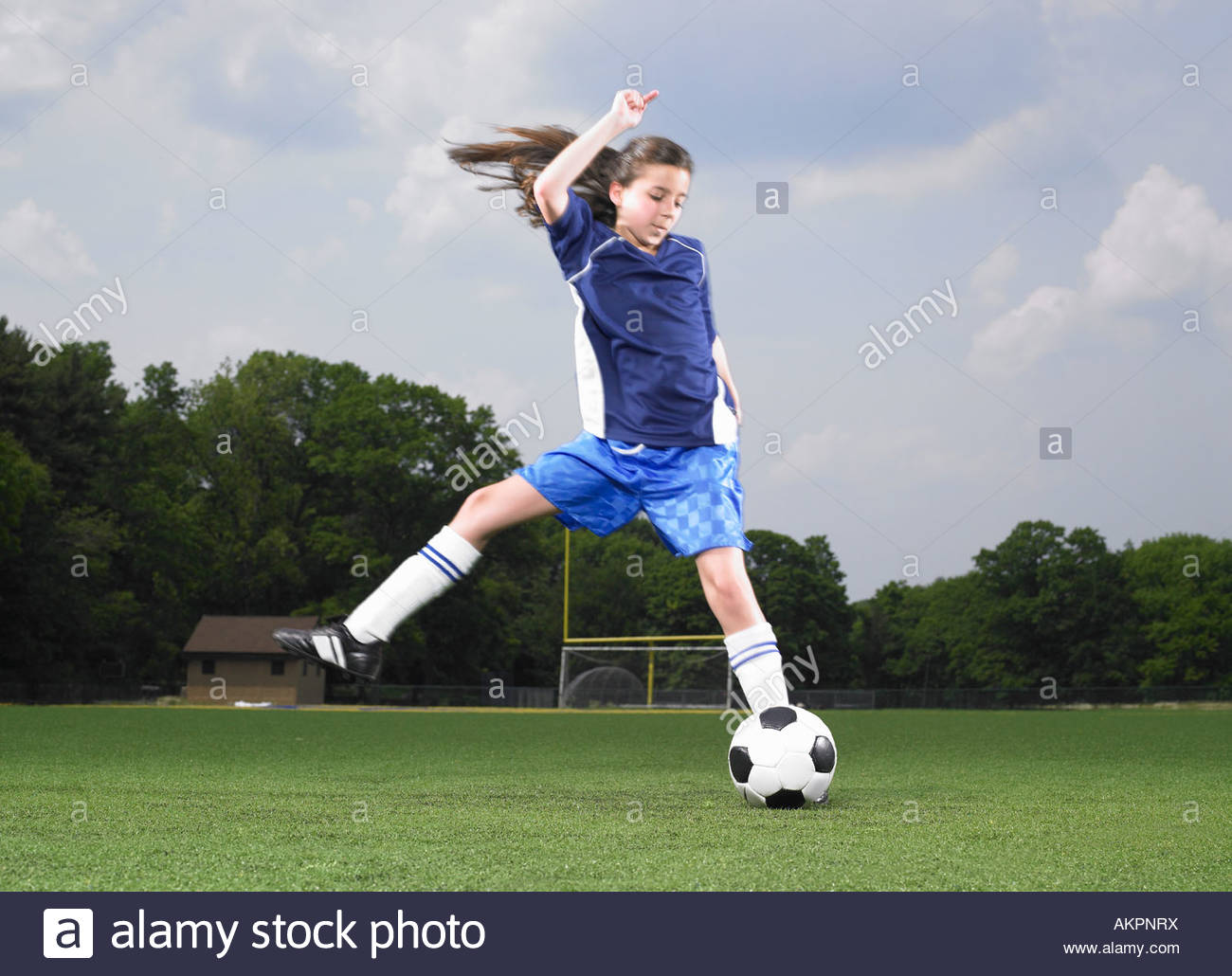 A footballer kicking a football - Stock Image