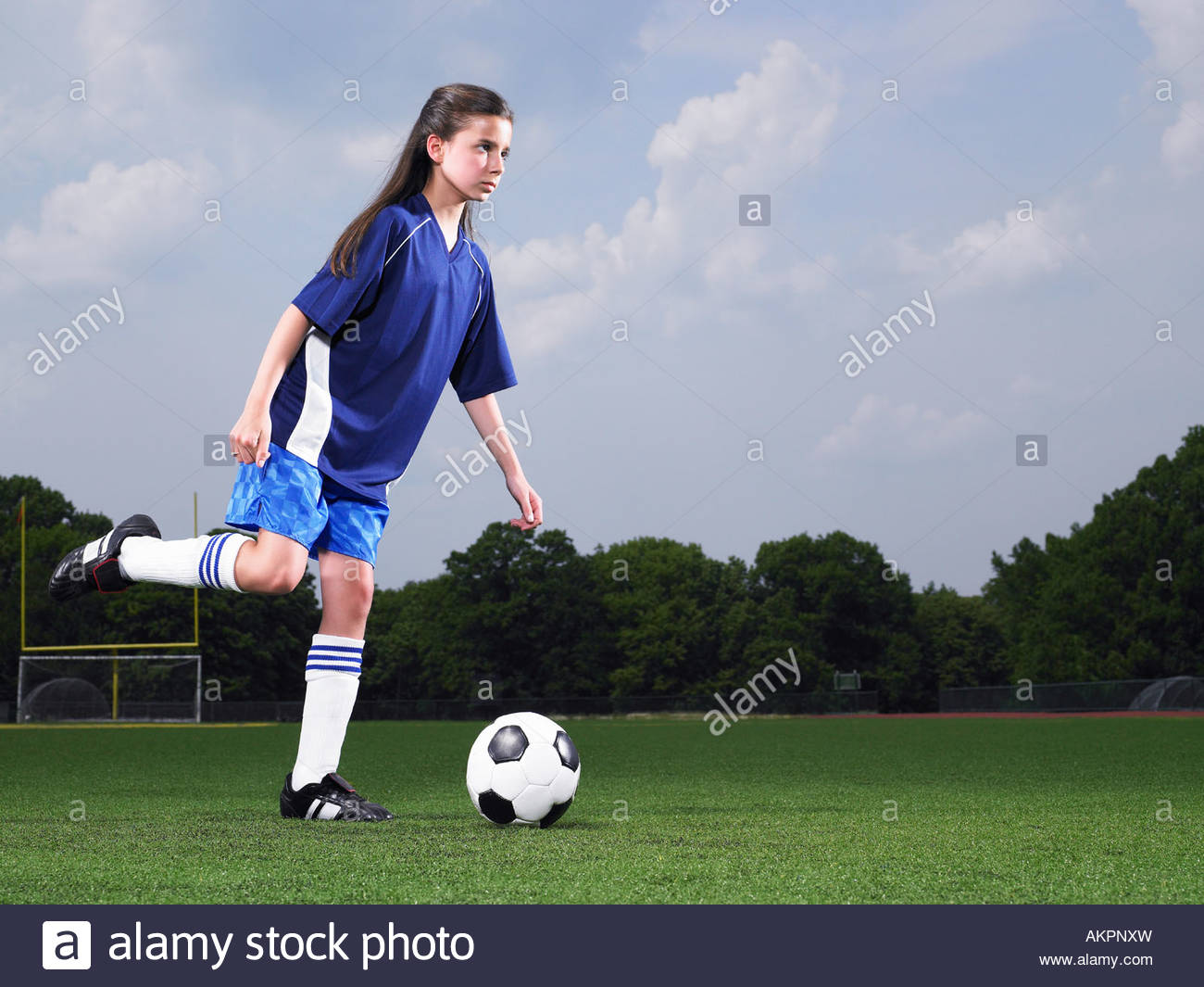 A footballer about to kick a football - Stock Image