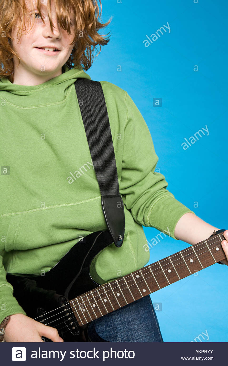 A teenage boy playing a guitar - Stock Image