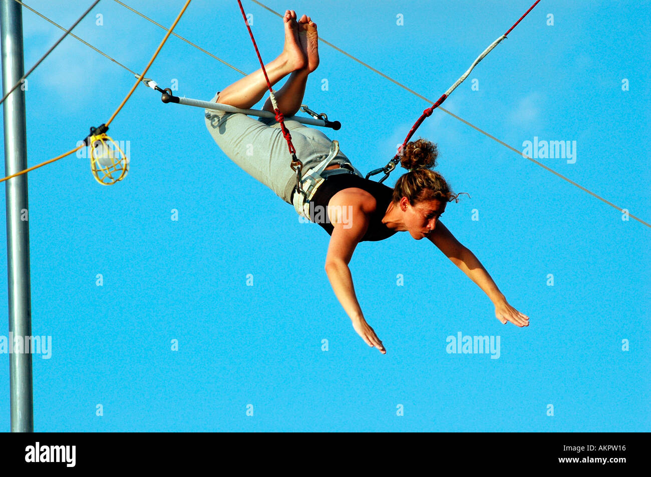 People swing on the trapeze at The Trapeze School at Hudson River Park - Stock Image