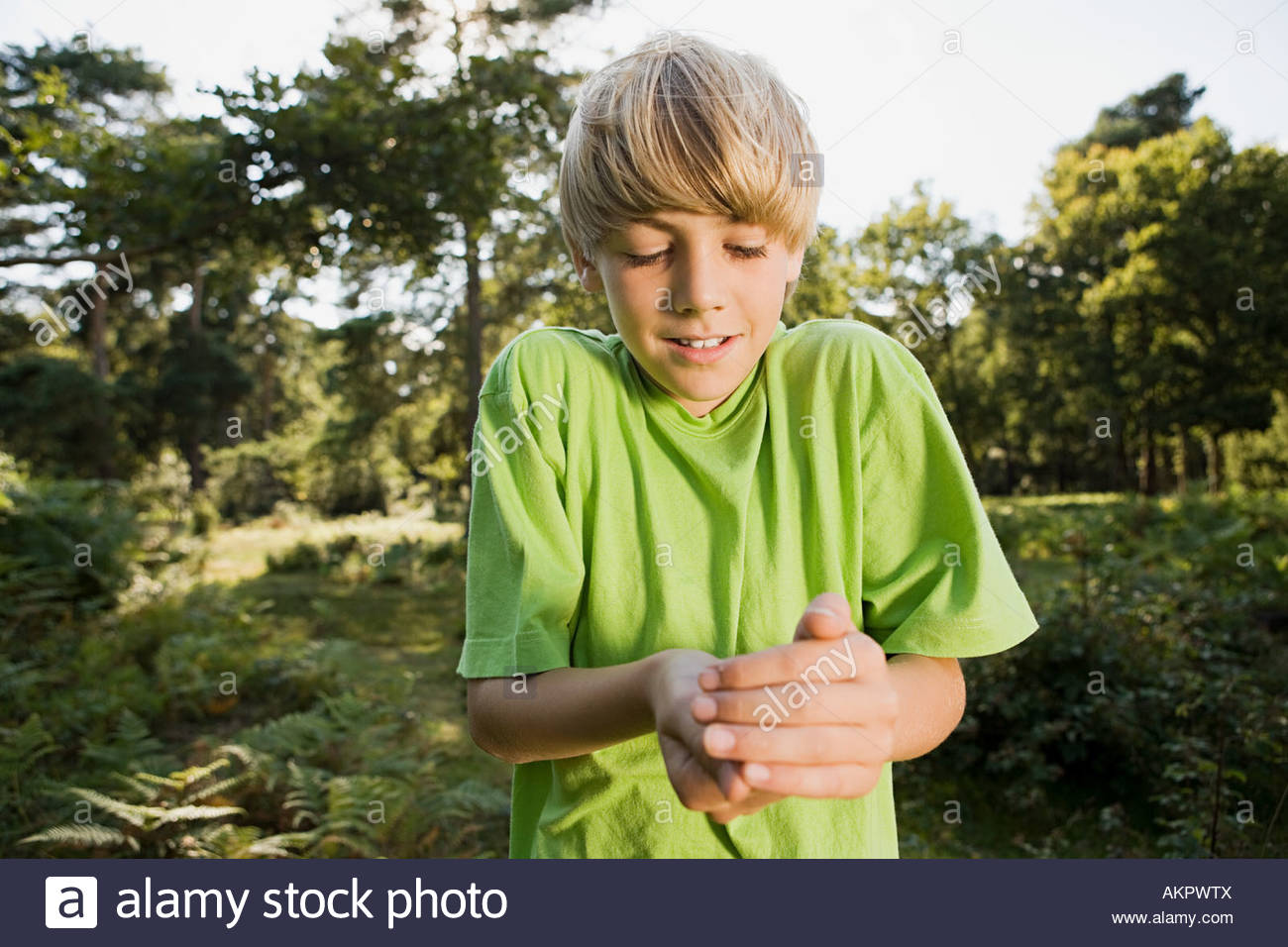 Boy holding something in his hands - Stock Image