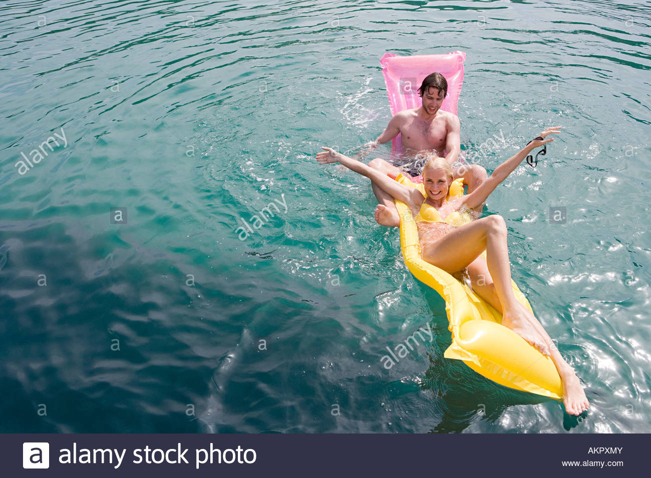 A couple fooling around on inflatable mattresses - Stock Image