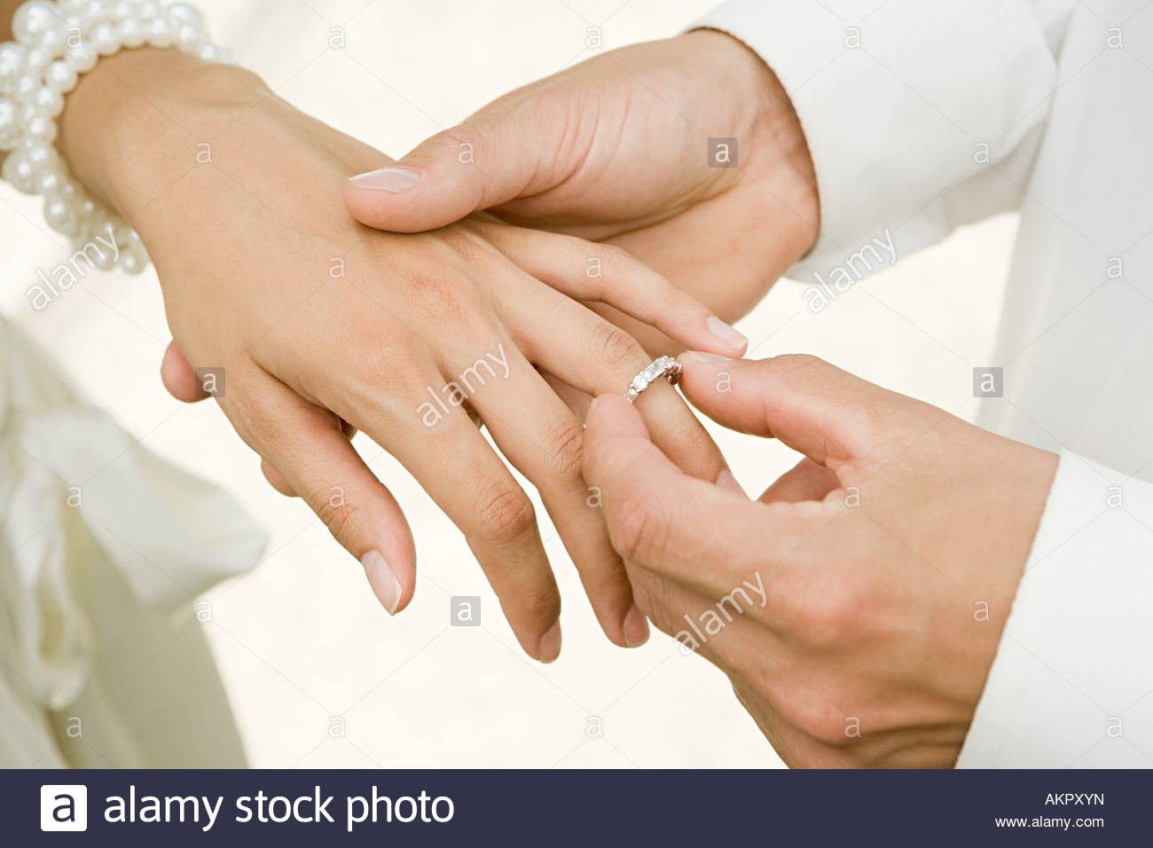 Man placing wedding ring on brides finger - Stock Image