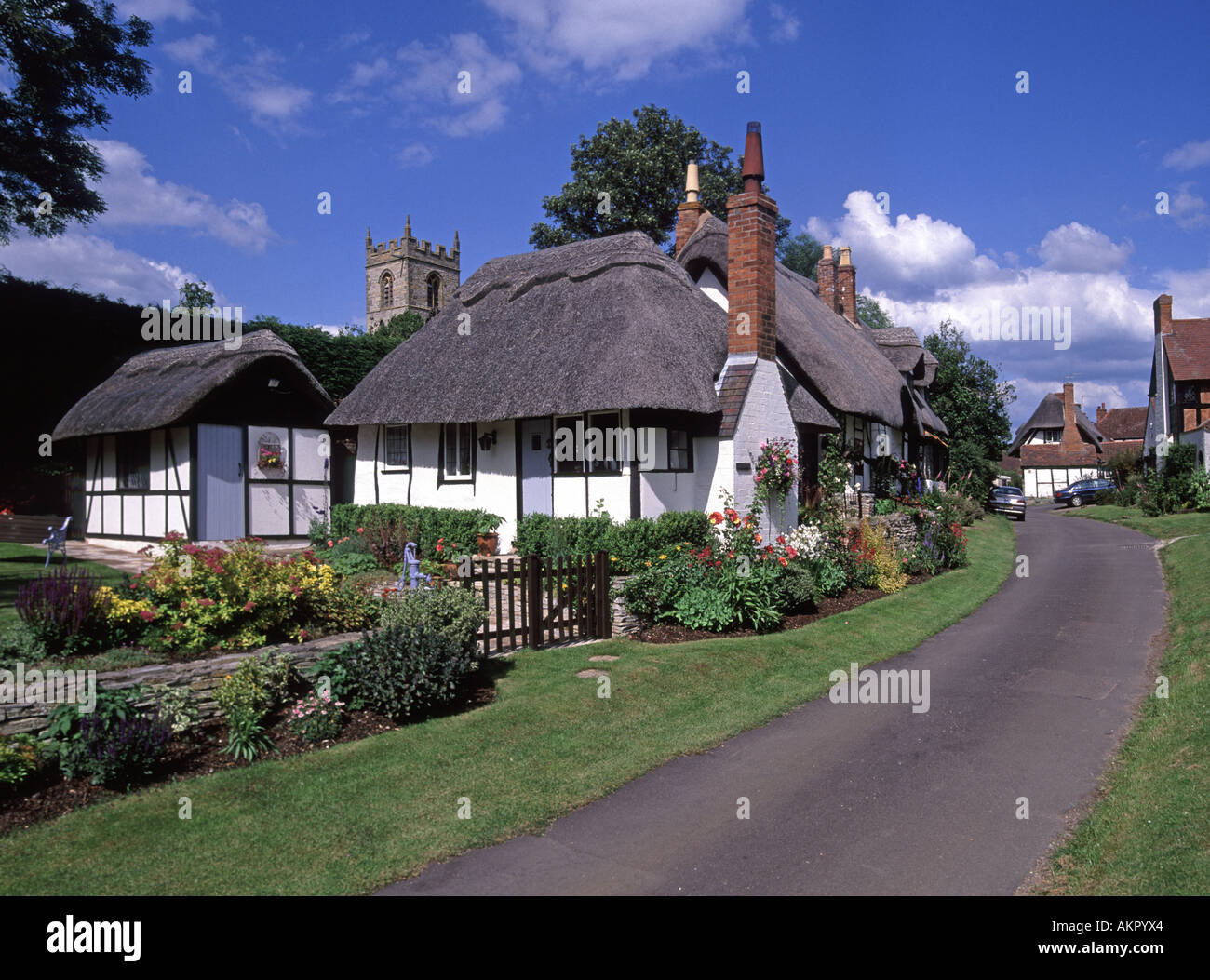 Welford On Avon Warwickshire village thatched cottage with church tower beyond some cables aerials & similar digitally removed - Stock Image
