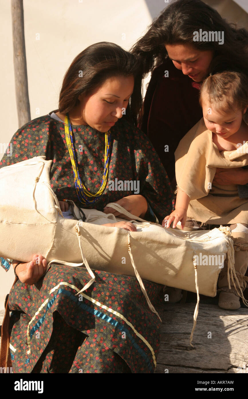 A young Native American Indian women with her baby in a cradle and another mom and her baby girl visiting - Stock Image