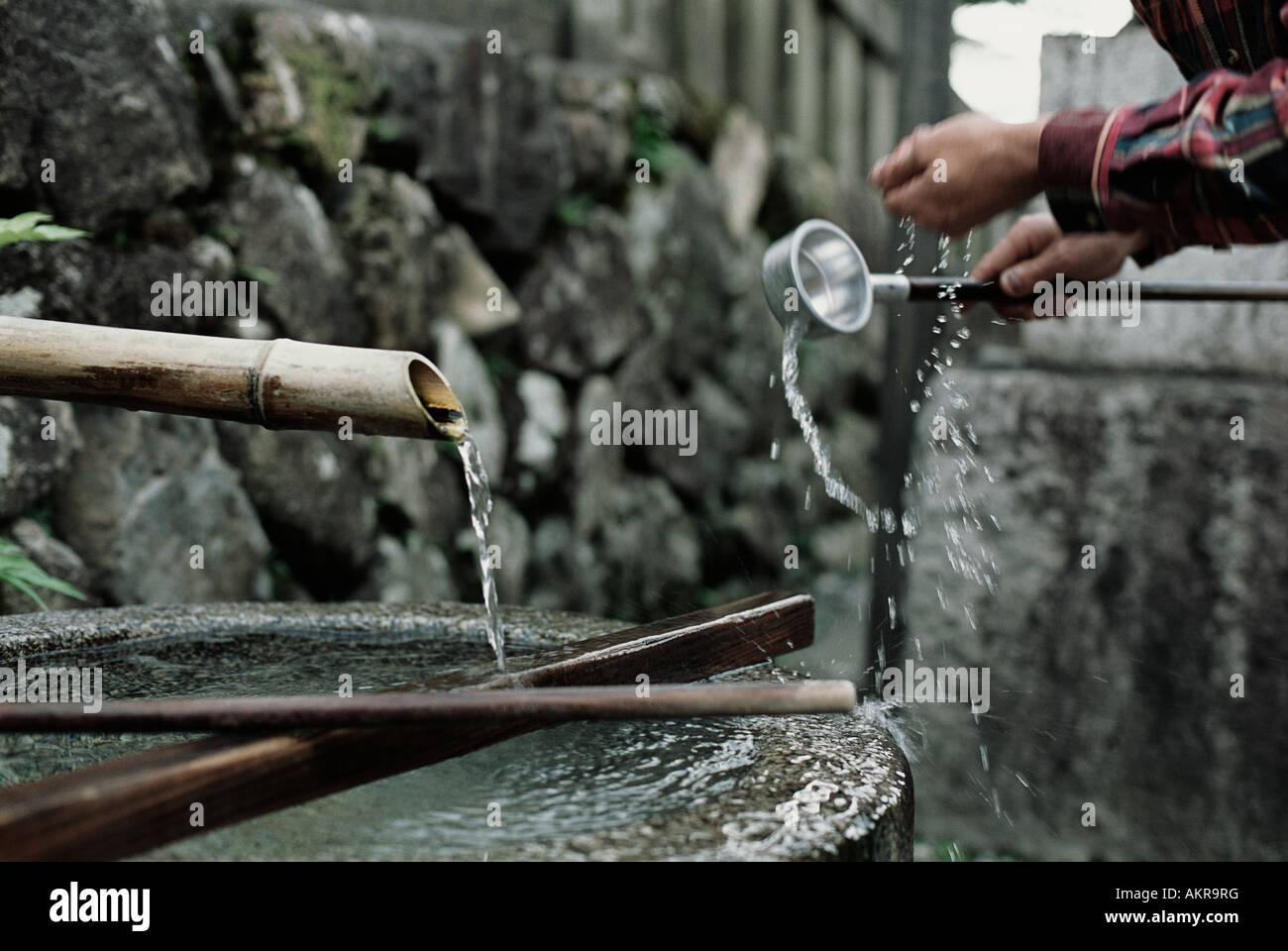 Person with water at temple - Stock Image
