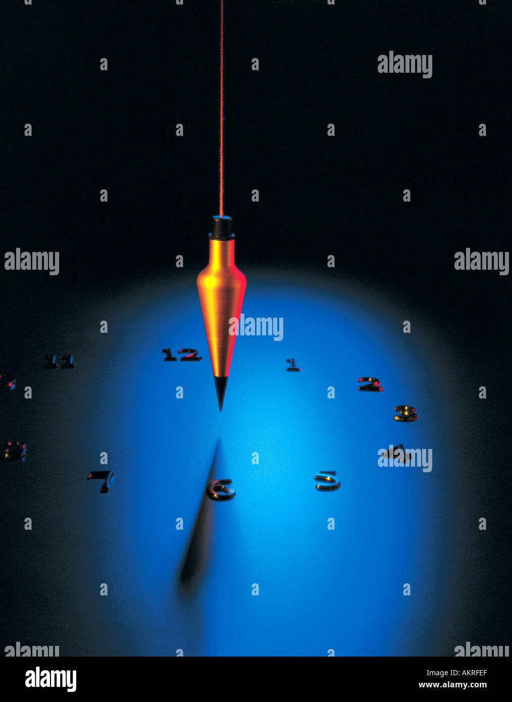 Plumbob plum bob with clock numerals on blue surface Stock Photo