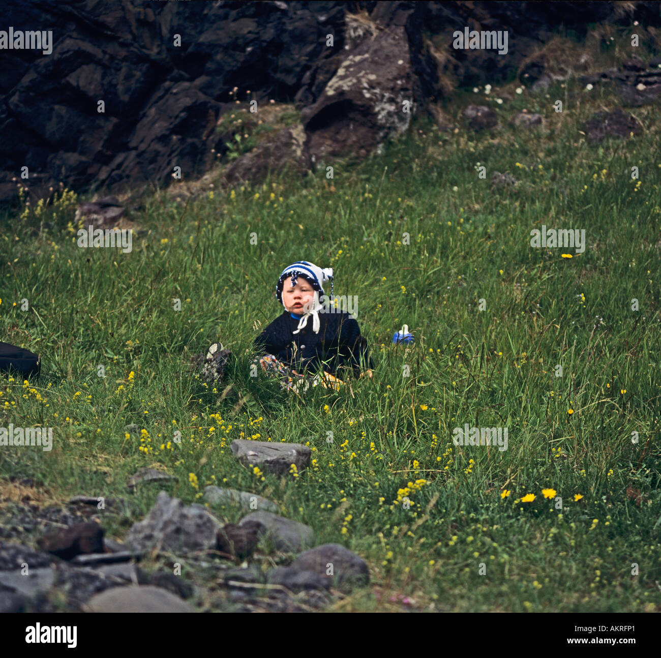 ICELAND EUROPE July Ten month old Icelandic boy with chubby red cheeks sitting in the grass - Stock Image
