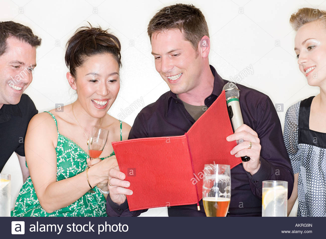 Four people choosing a karaoke song - Stock Image