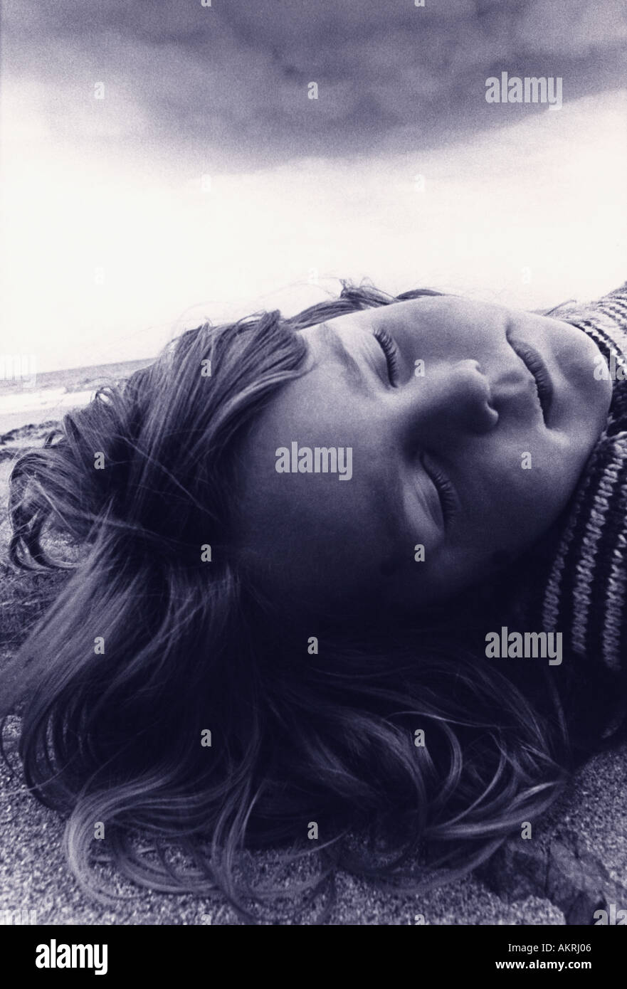 Girl asleep on beach - Stock Image