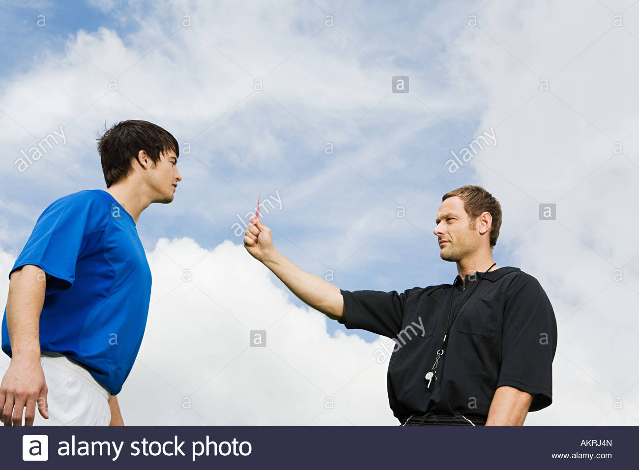 A referee showing a footballer a red card - Stock Image