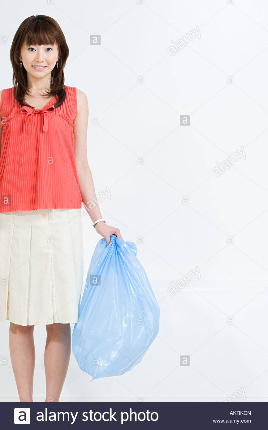 A woman holding a rubbish bag - Stock Image