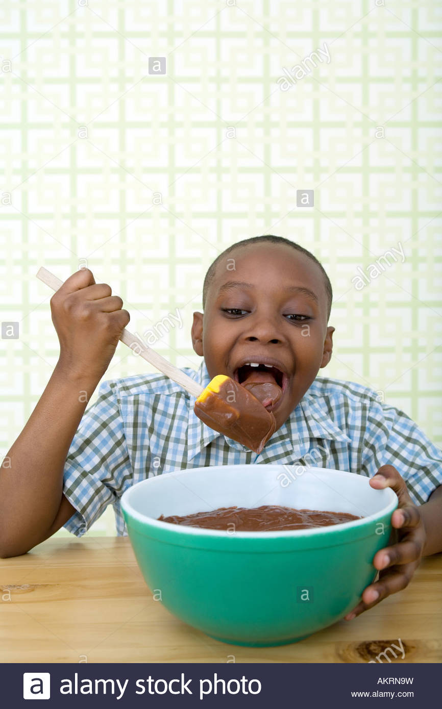 Boy eating melted chocolate from a spatula - Stock Image