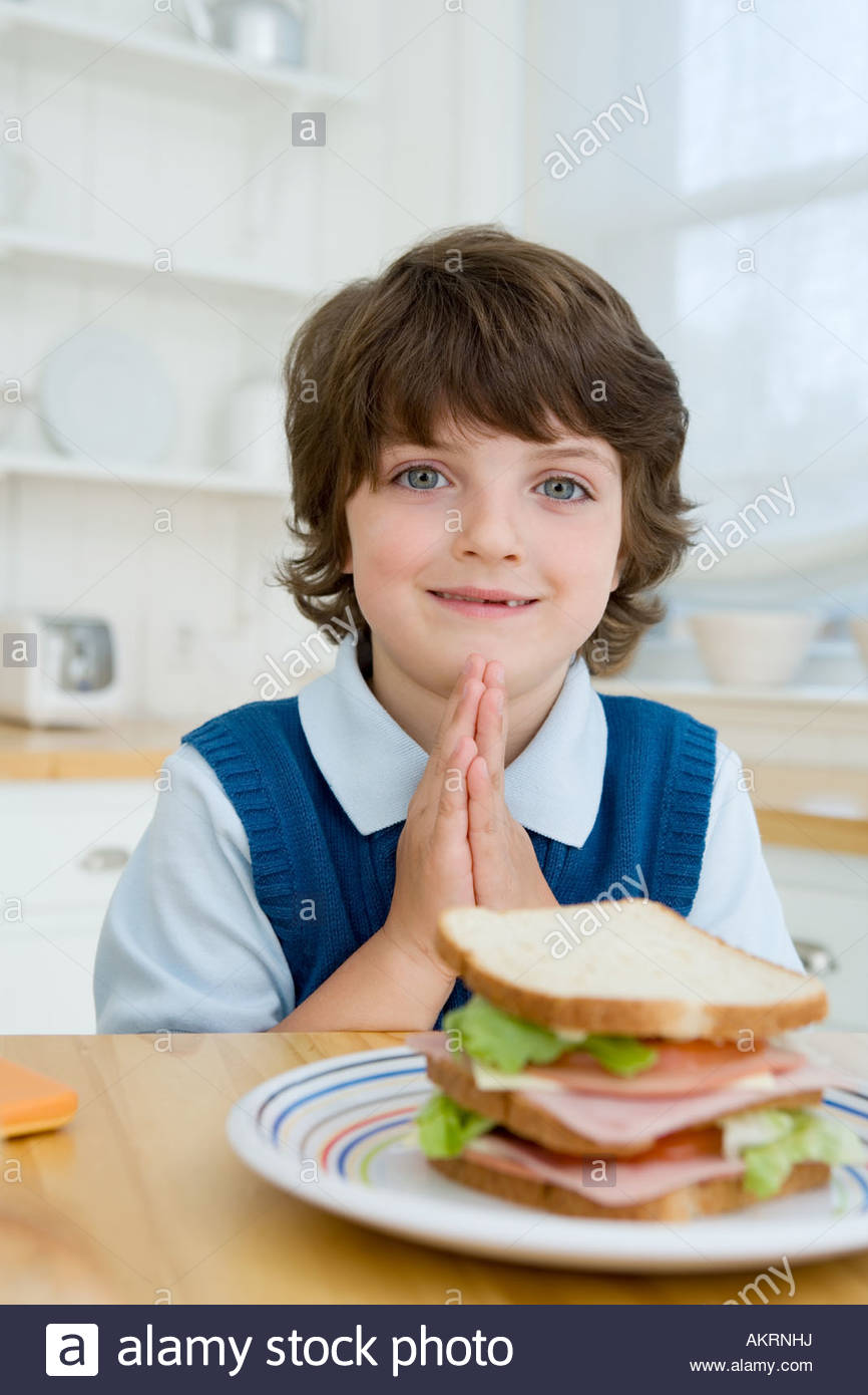 Boy saying grace - Stock Image