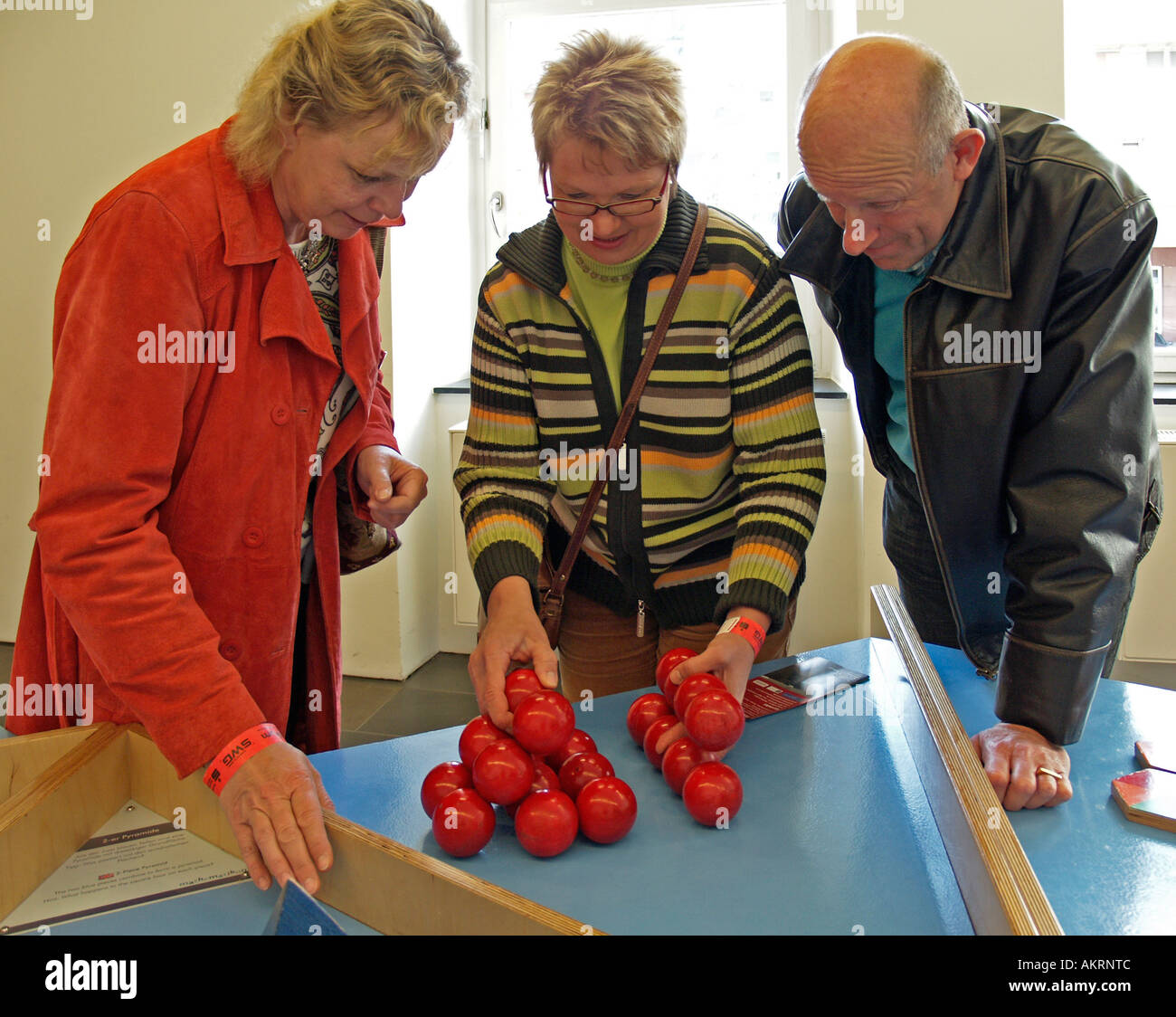 persons trying to build a pyramid play for the intelligence in the museum Mathematikum Giessen Germany Stock Photo