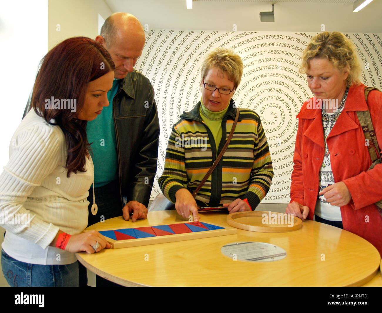 persons trying to put different pieces to a correct patter play for the intelligence in the museum Mathematikum Stock Photo