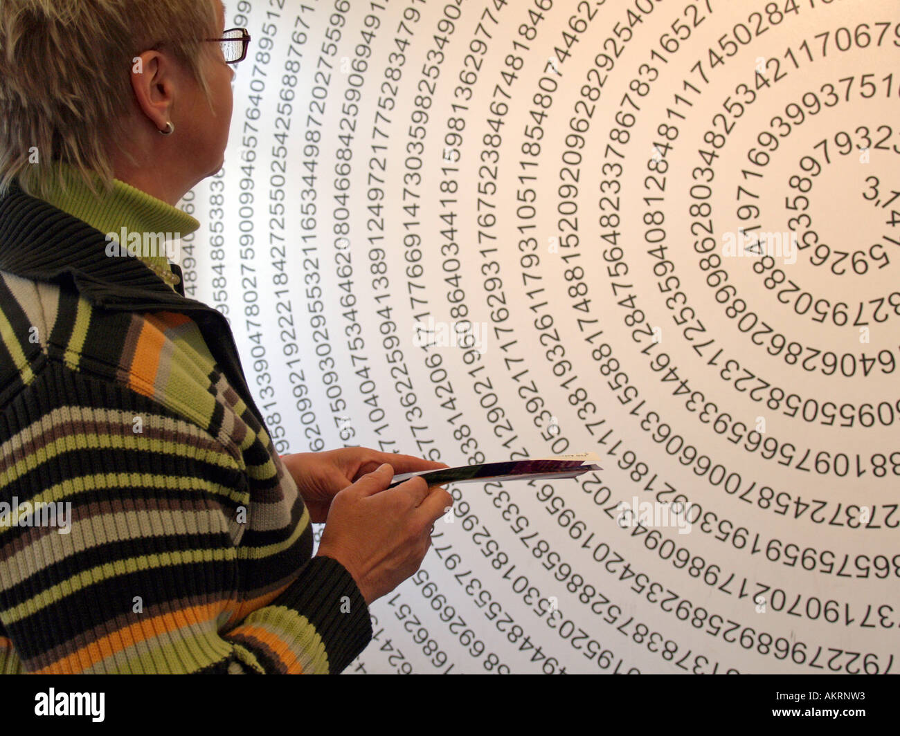 woman looking a drawing with the endless number of Pi in form of a helix on the wall in the museum Mathematikum Stock Photo