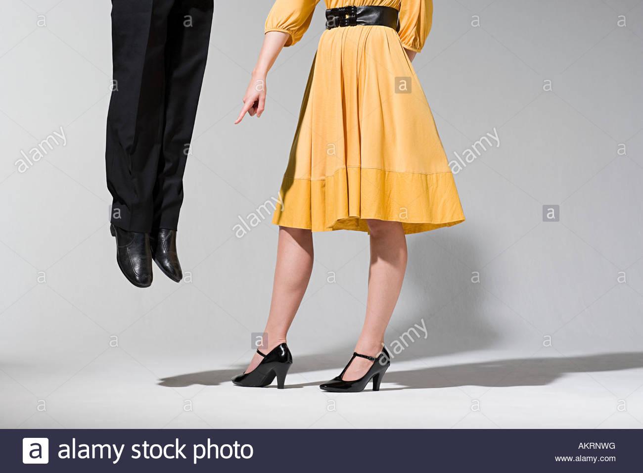 A woman pointing at man jumping - Stock Image